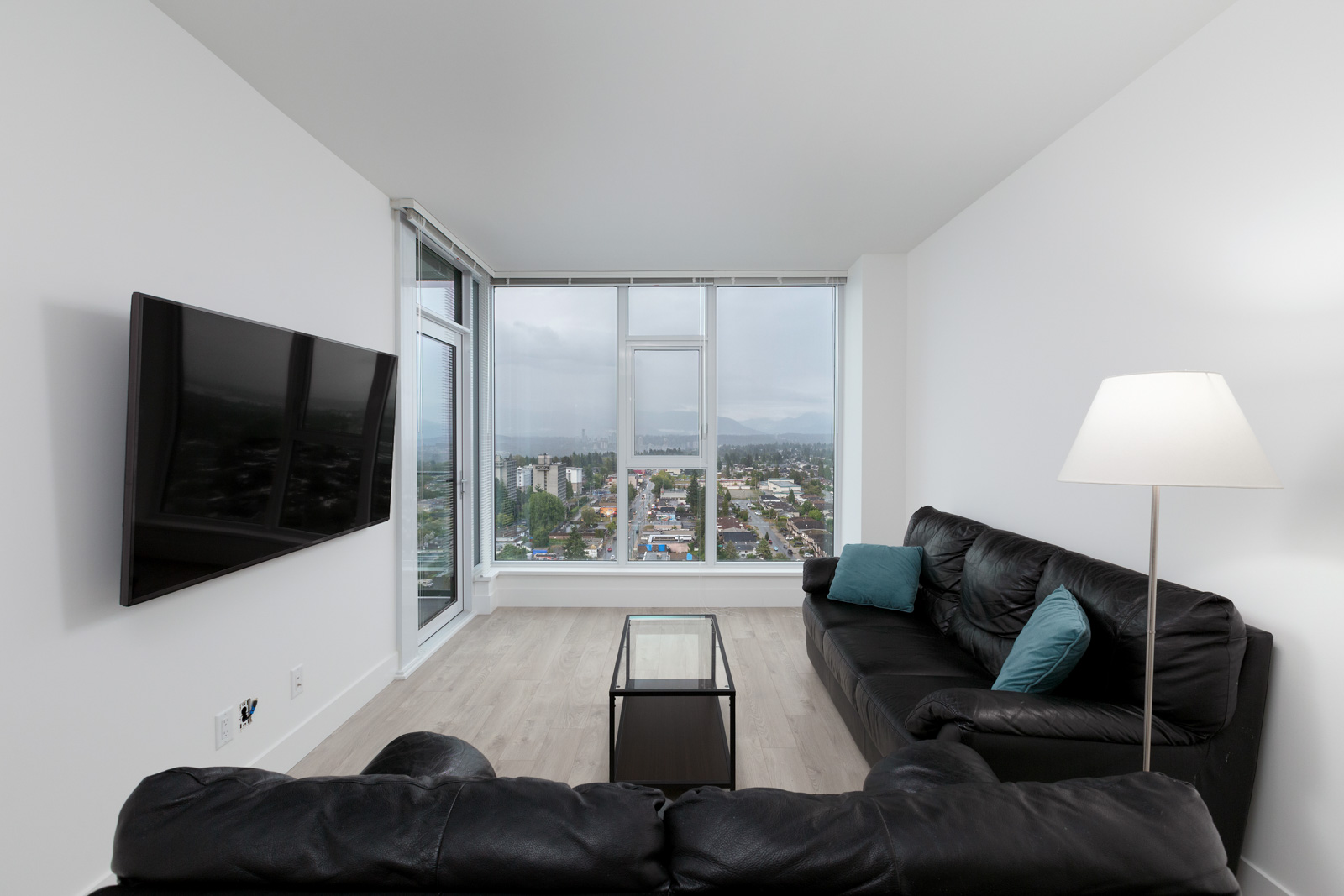 llving room of rental condo at kings crossing three in burnaby with window and view in background