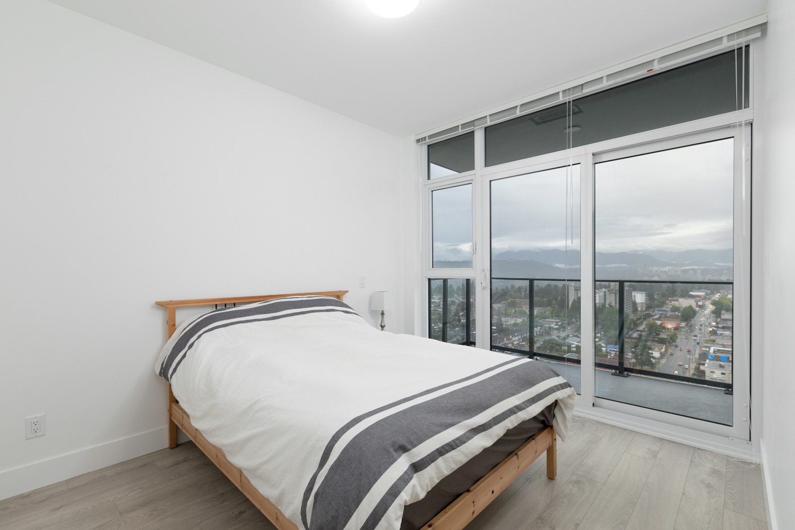bed in bedroom of rental condo in burnaby with windows on left