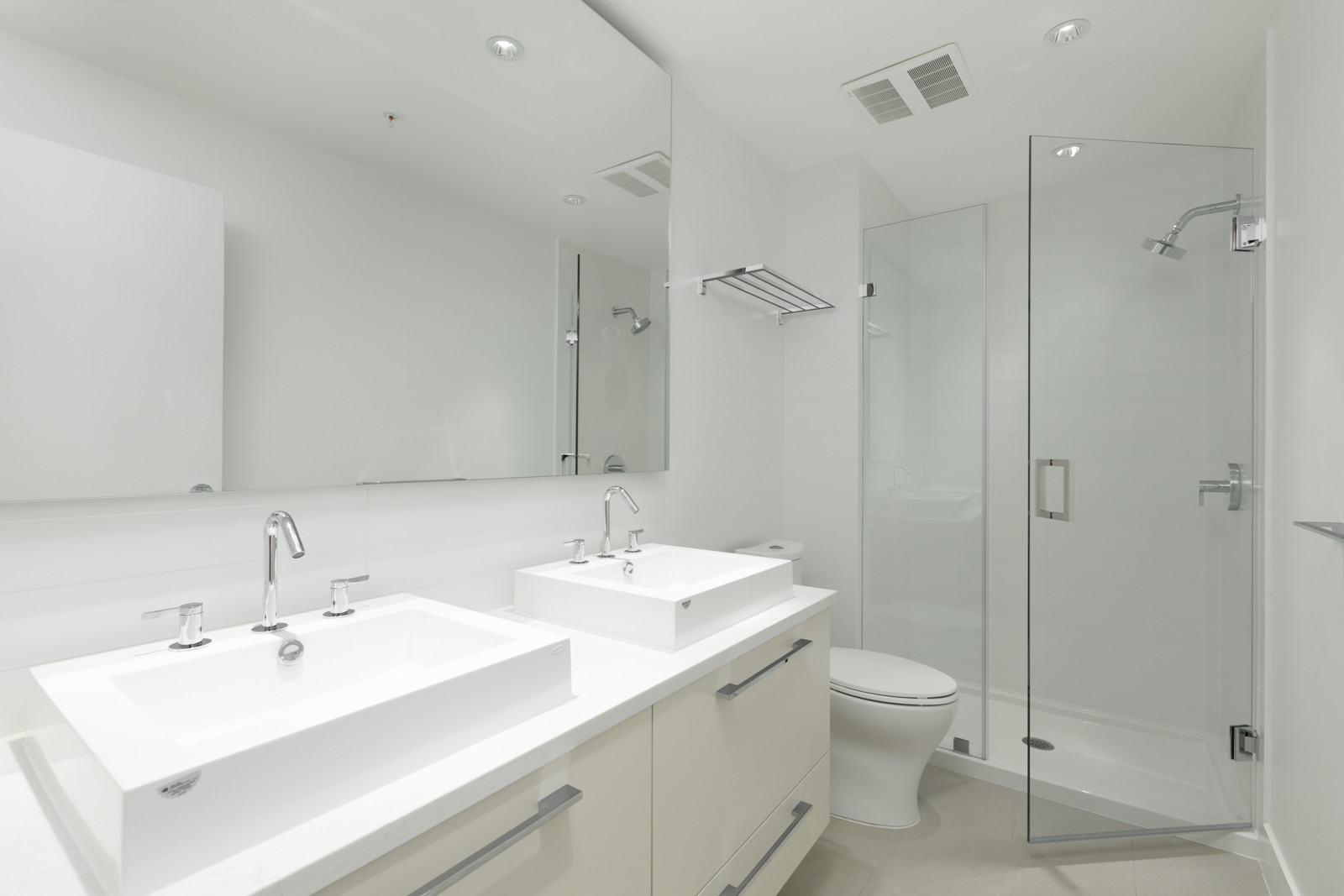 bathroom of rental condo in burnaby with mirror and two basins and counter on left and shower on right