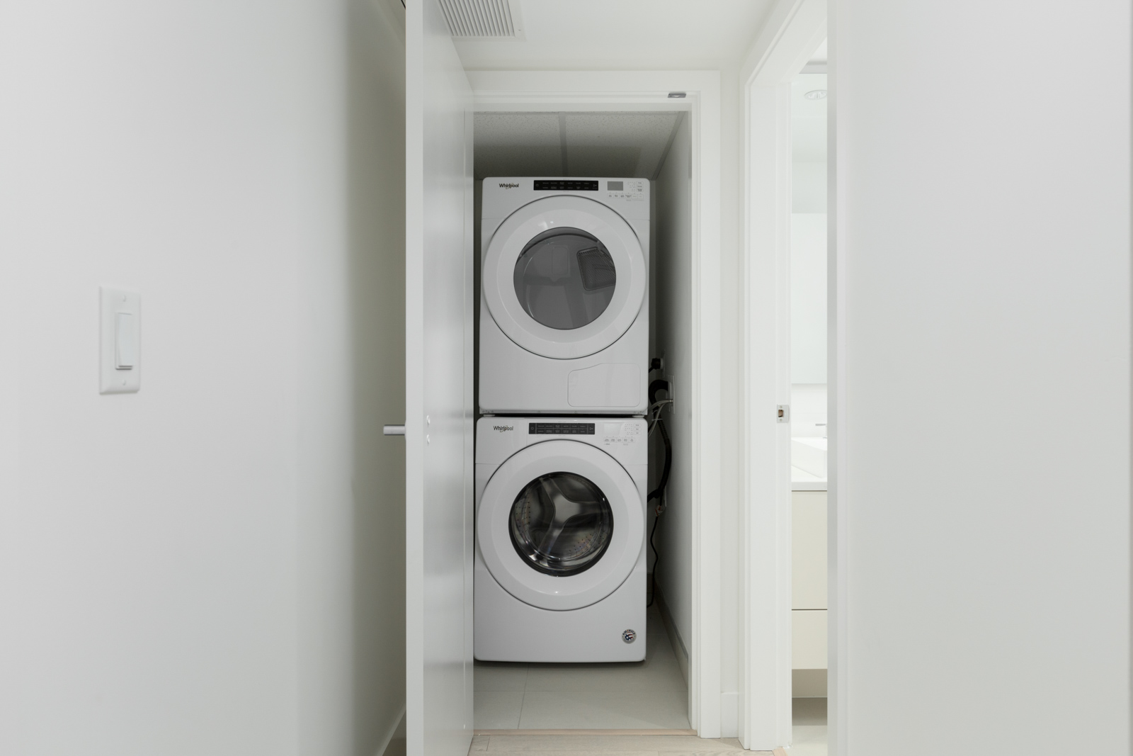 stacked washer and dryer in laundry closet of rental condo in kings crossing three building in burnaby highgate village
