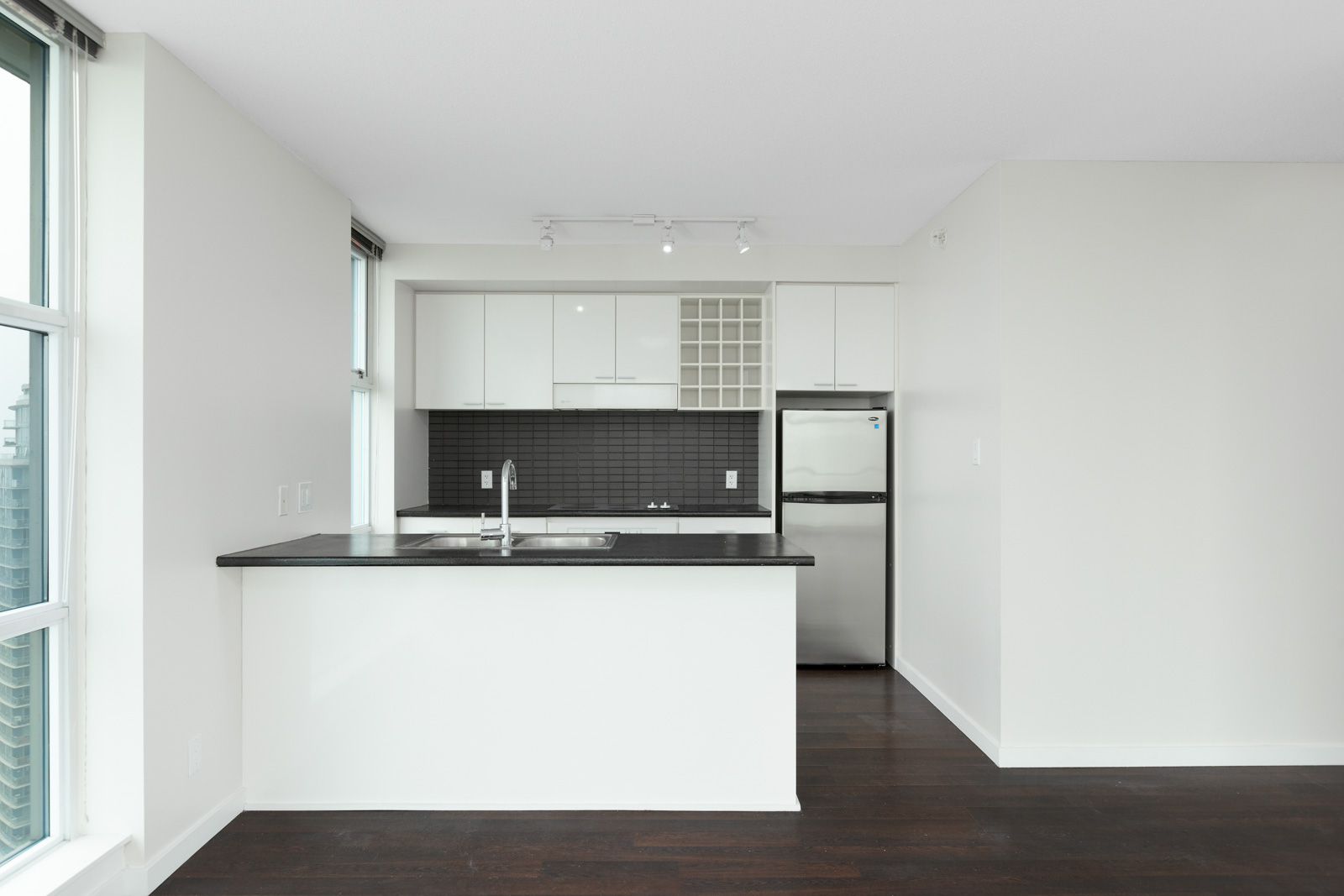 kitchen with counter and stainless steel refrigerator in rental condo at spectrum 4 in chinatown vancouver