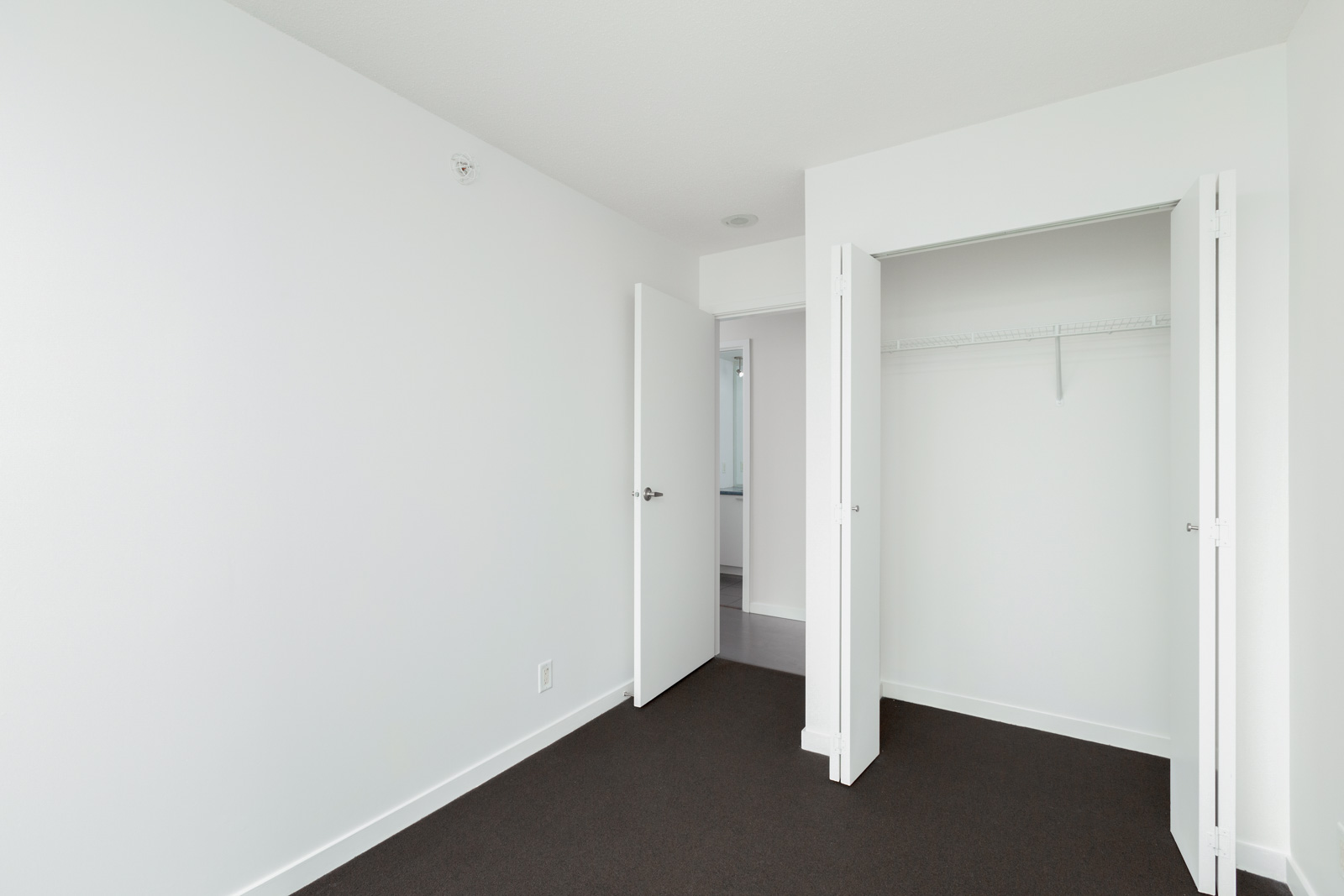 bedroom with closet on right and entrance door on left in rental condo in spectrum building in chinatown vancouver