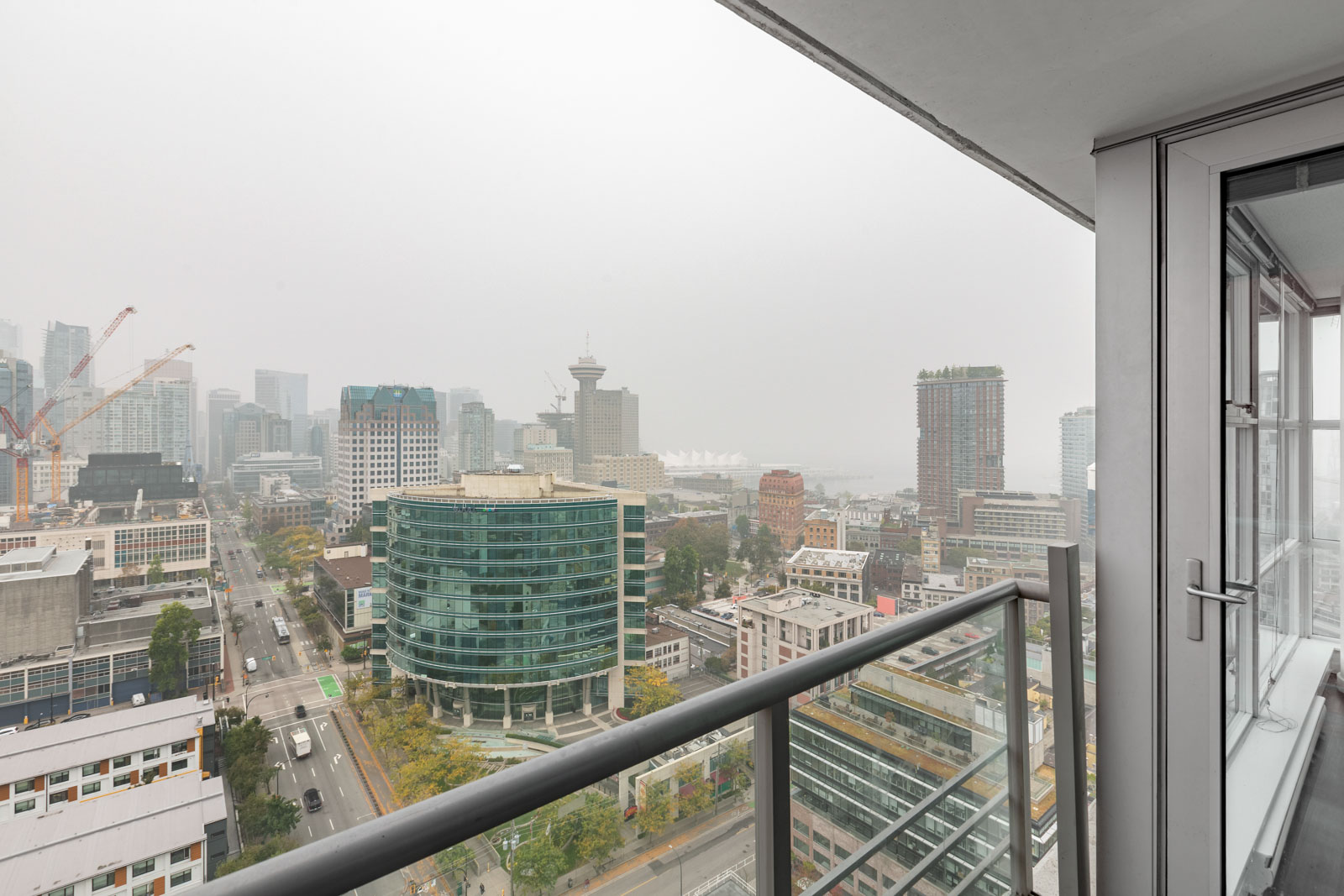 bathroom in rental condo with views of other condo buildings on a cloudy day in spectrum building in chinatown vancouver