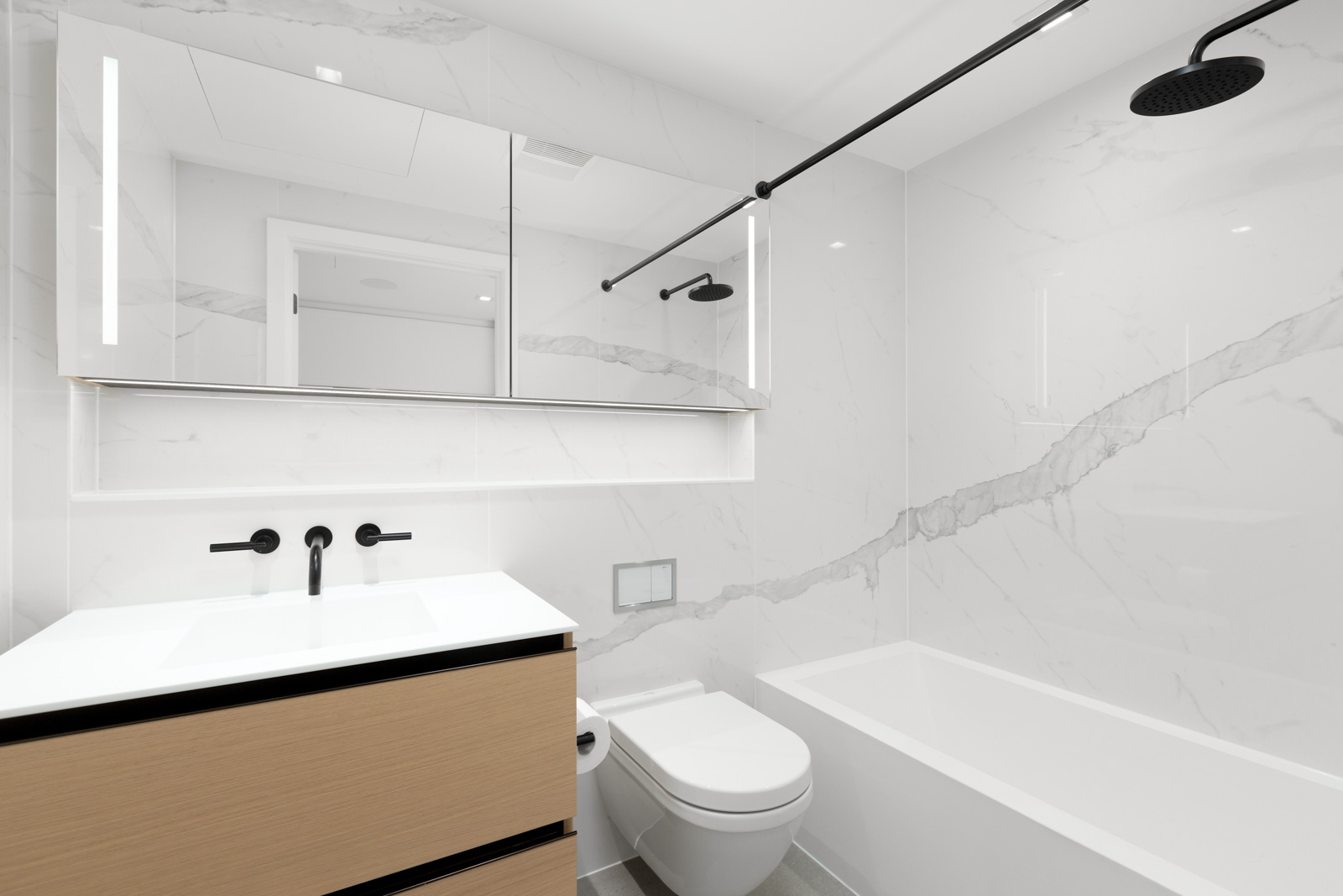 vanity on left and toilet and bathtub on right of bathroom in rental condo in coal harbour neighbourhood in downtown vancouver