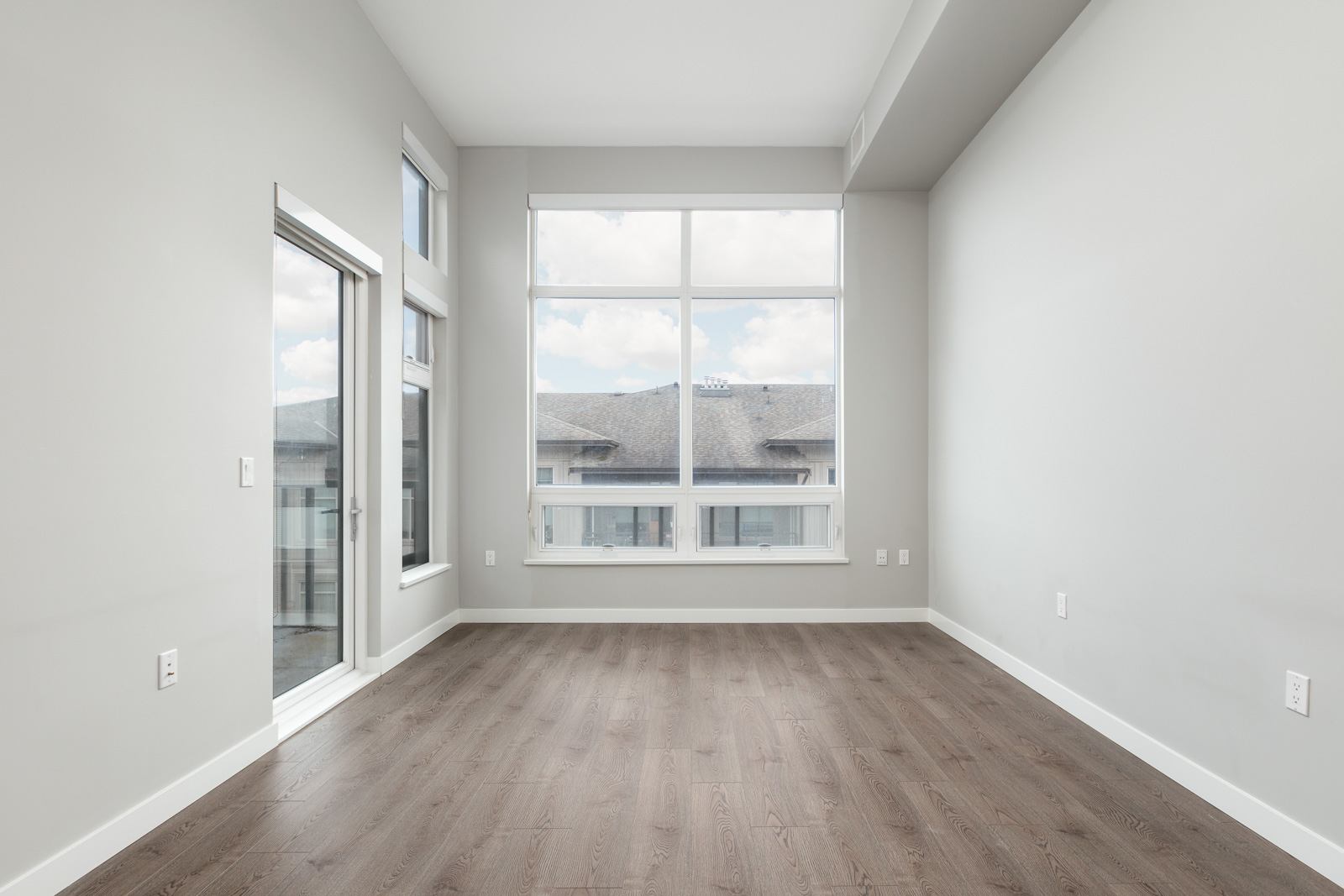 den with white walls and hardwood floors and floor to ceiling windows in rental townhome in Richmond