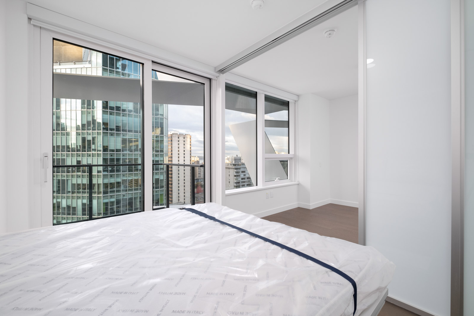 bedroom with white walls and window in rental condo at cardero in coal harbour neighbourgood of vancouver
