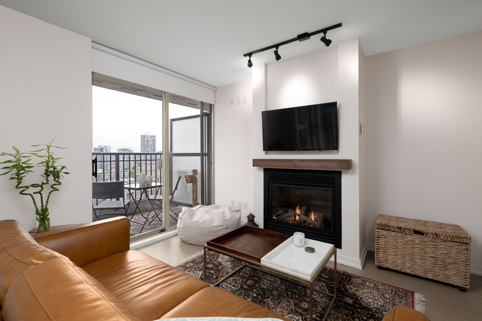 living room with balcony of rental condo fully furnished with tv fireplace and couch at mondrian 2 building in yaletown neighbourhood of downtown vancouver