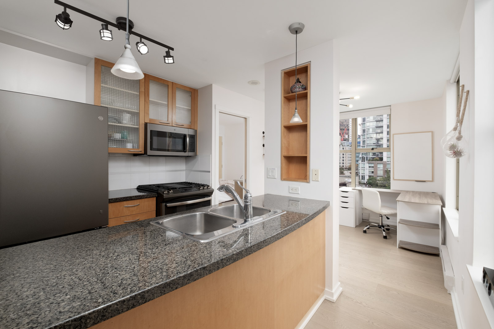 kitchen with stove fridge and island in rental condo fully furnished at mondrian 2 building in yaletown neighbourhood of downtown vancouver
