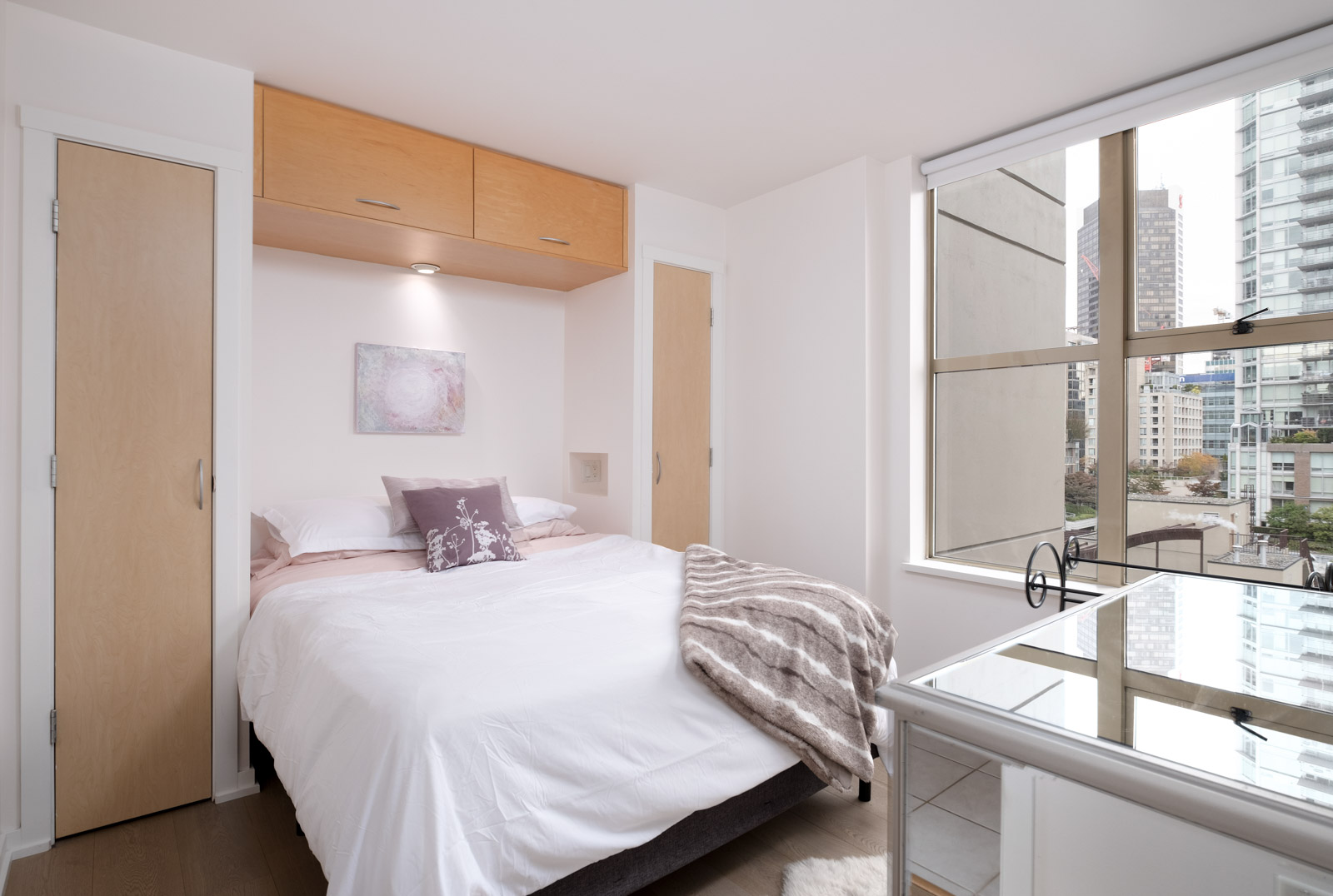 bed and dressor in rental condo at mondrian 2 in yaletown neighbourhood of downtown vancouver