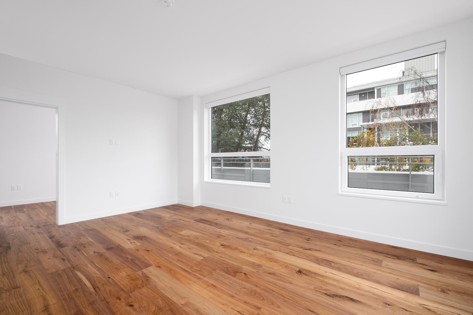 room with windows and white walls and hardwood floors in vancouver westside rental condo managed by birds nest properties
