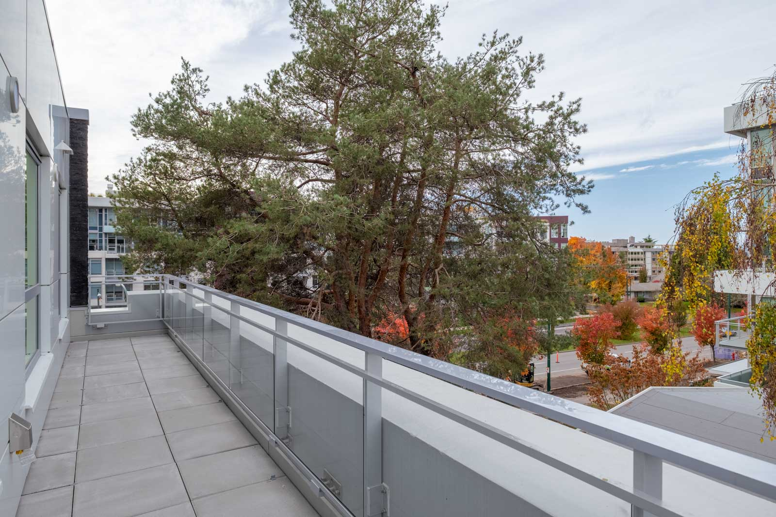 balcony with view of tree from rental condo in basalt building developed by pennyfarthing homes and managed by birds nest properties in vancouver canada
