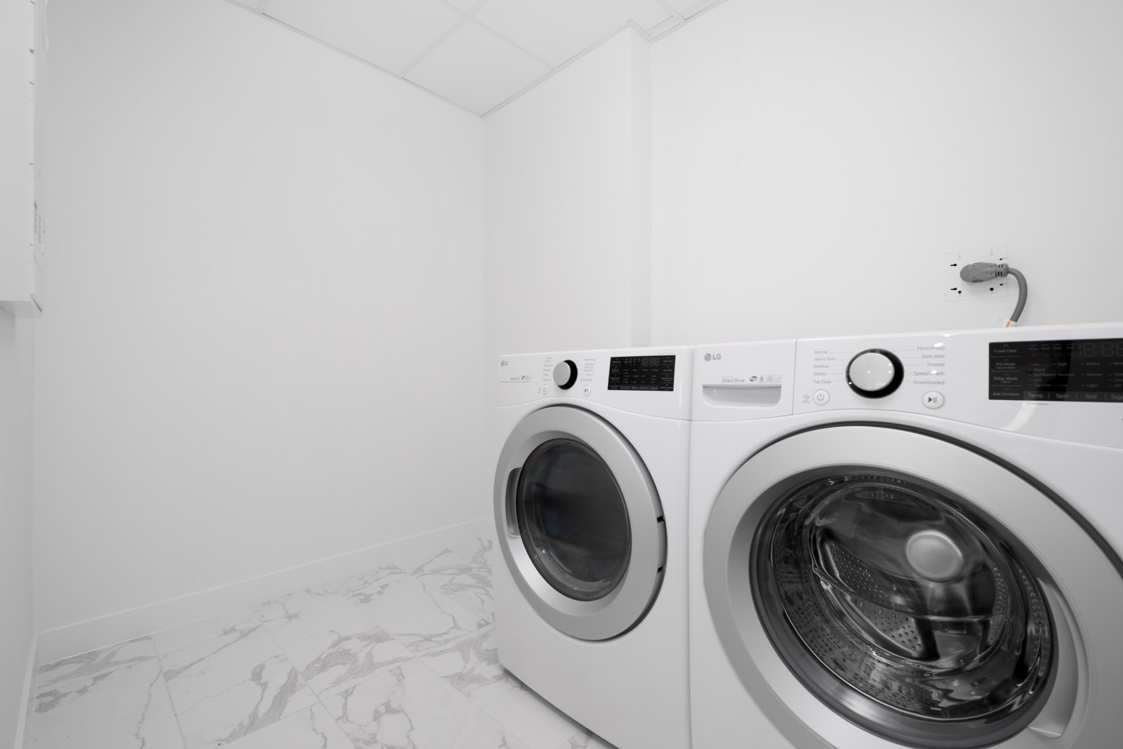 white washer and dryer side by side in laundry room with white walls in rental condo in vancouver