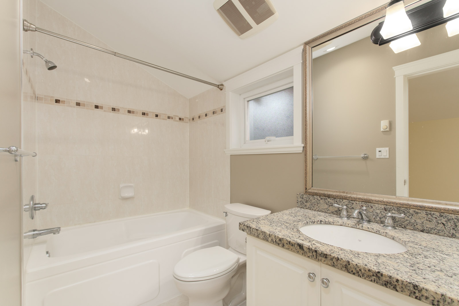 bathroom with vanity and mirror on right and bathtub in coach house for rent near commercial drive in east vancouver