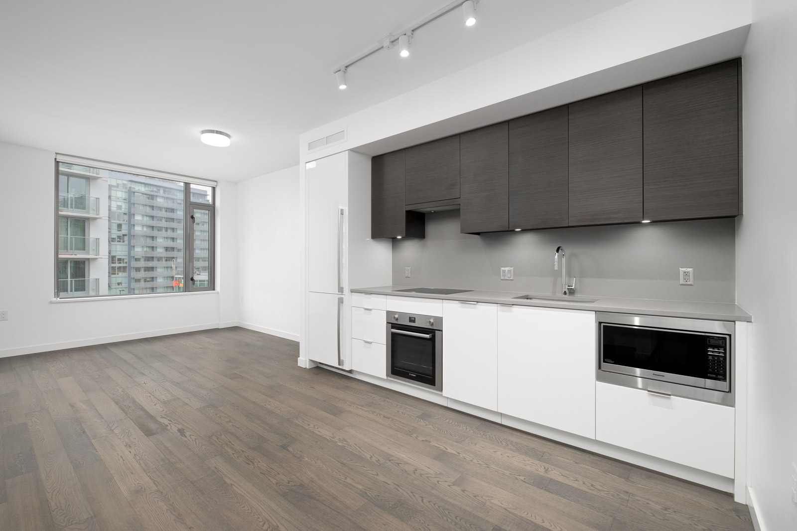 kitchen and living room in rental condo in navio on pullman porter street in false creek olympic village