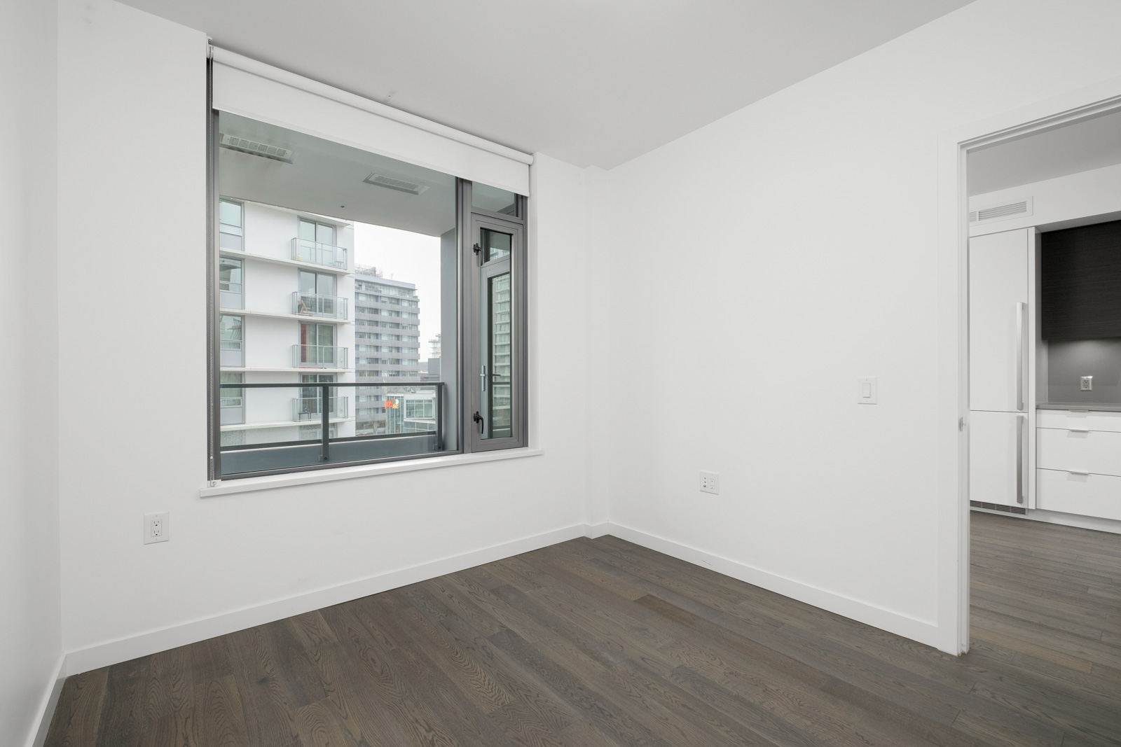 bedroom corner with hardwood floors and white walls and window on the left in false creek vancouver