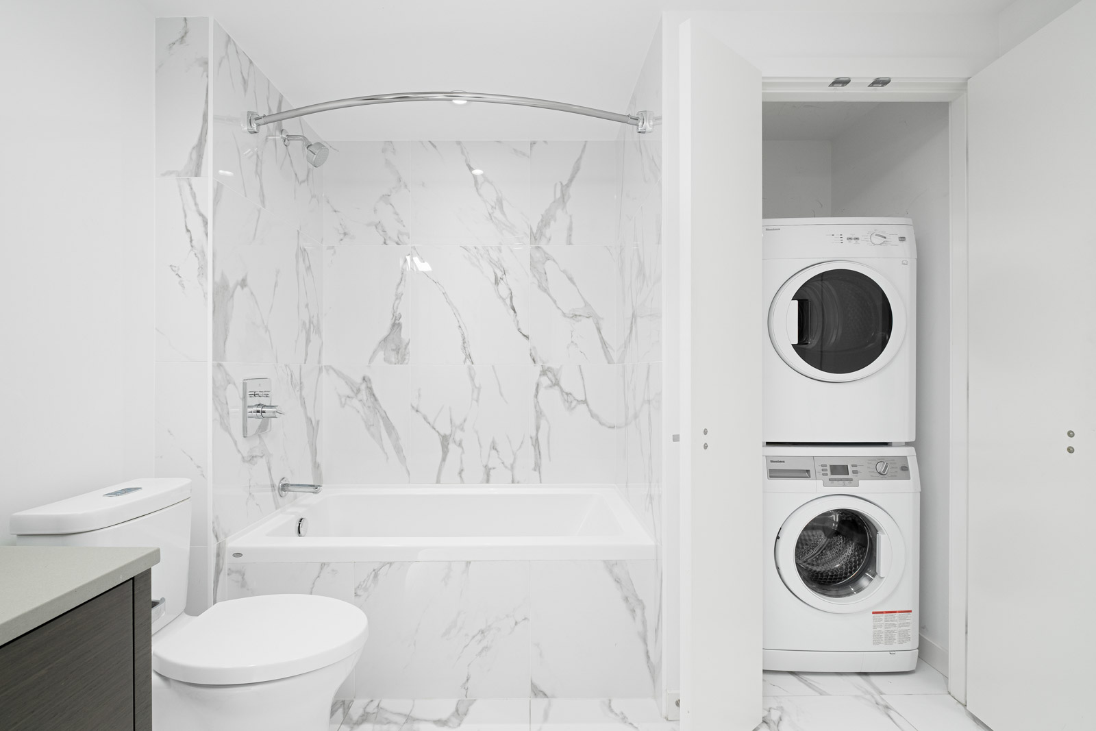 stacked white washer and dryer on right and bathroom on left with marble tiling in rental condo in navio