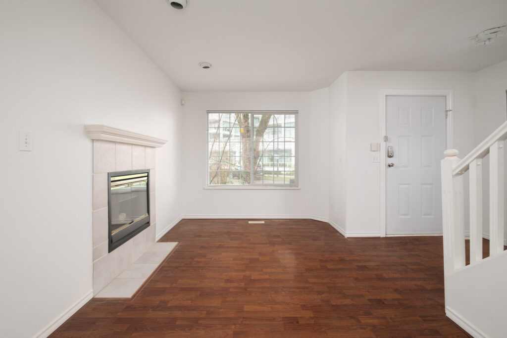 living room with fireplace on left and windows in background in rental house in east vancouver
