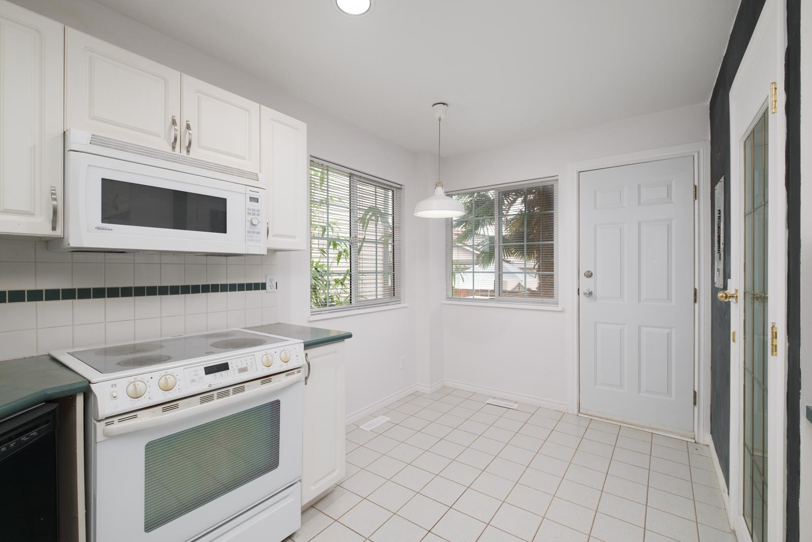 kitchen with over the top white microwave and white oven range on the left in east vancouver rental house