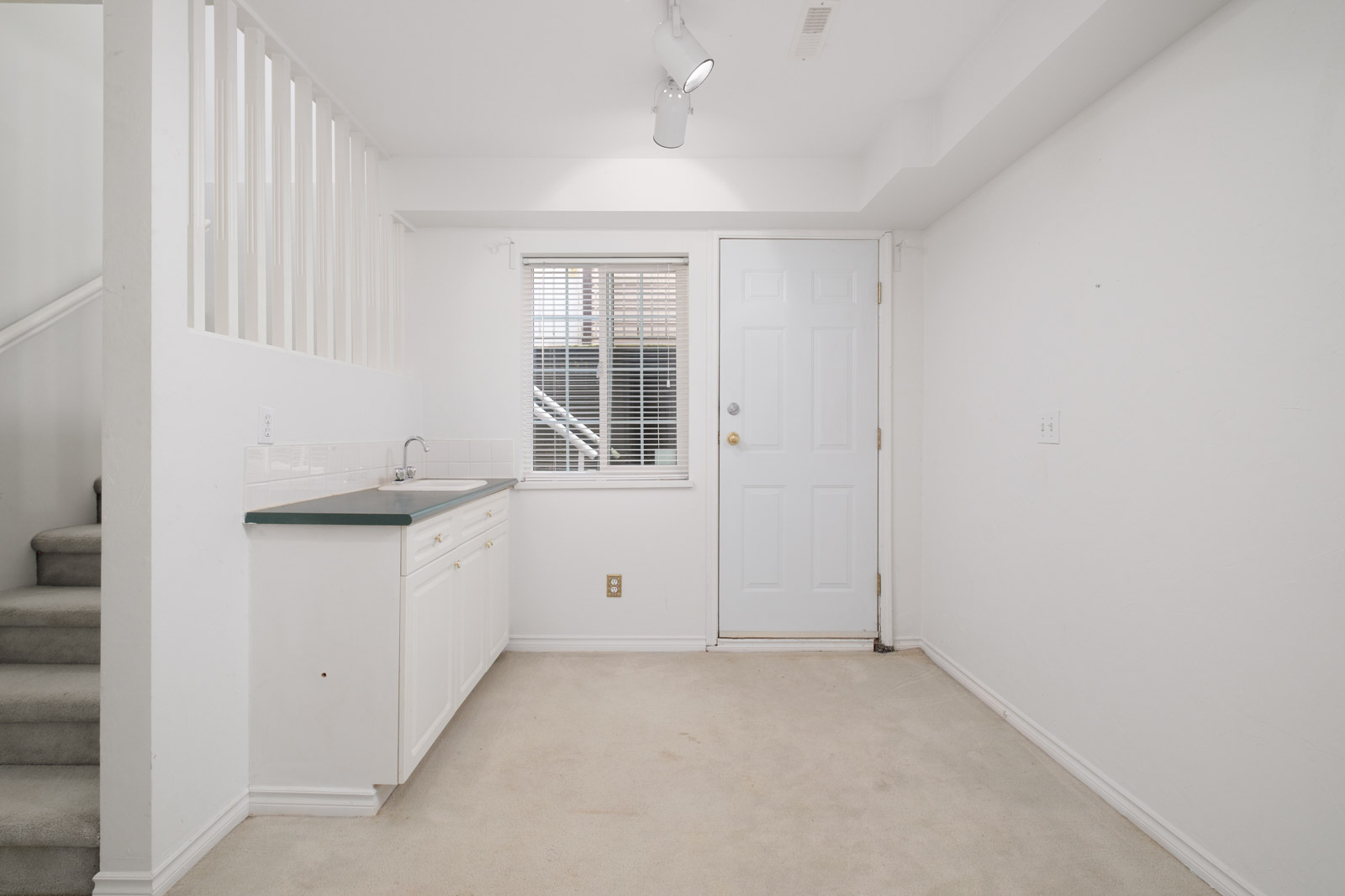 room with faucet and countertop on left and door with window in background with white walls in rental house in east vancouver