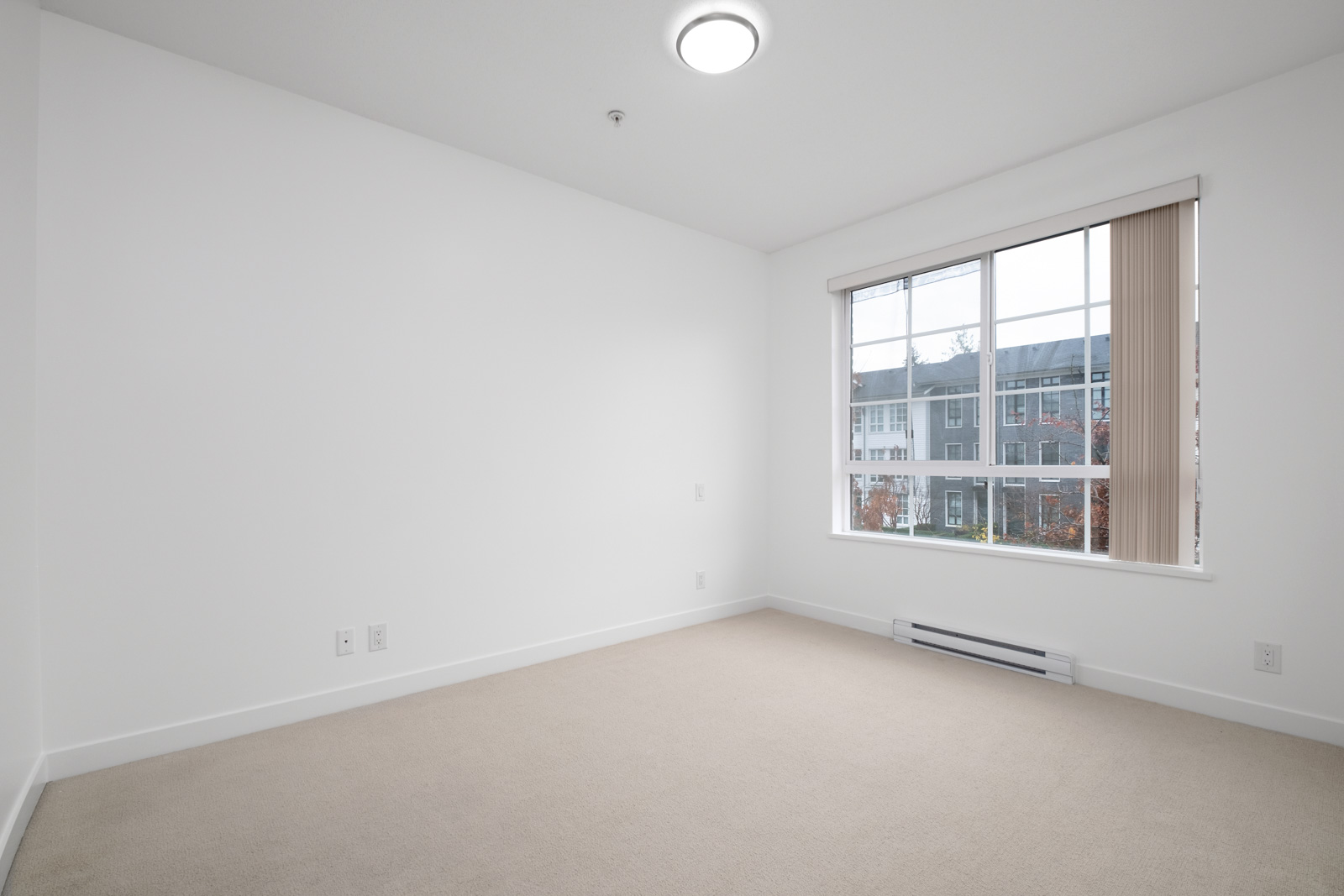 bedroom with white walls and window in rental condo in the Lougheed Town Centre neighbourhood of Coquitlam