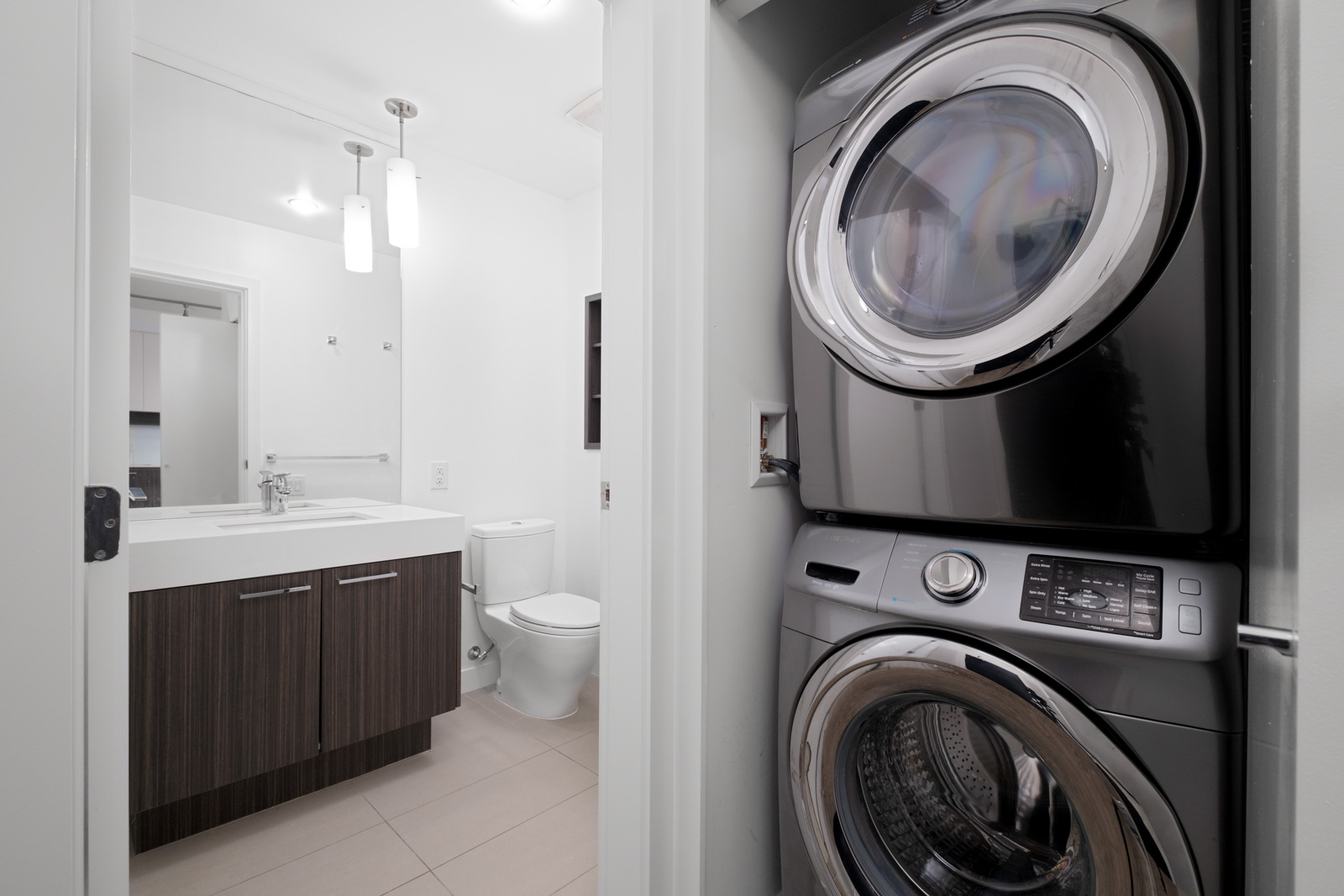 stacked washer and dryer on right and bathroom with vanity mirror and toilet on left in rental condo in lougheed heights neighbourhood of coquitlam
