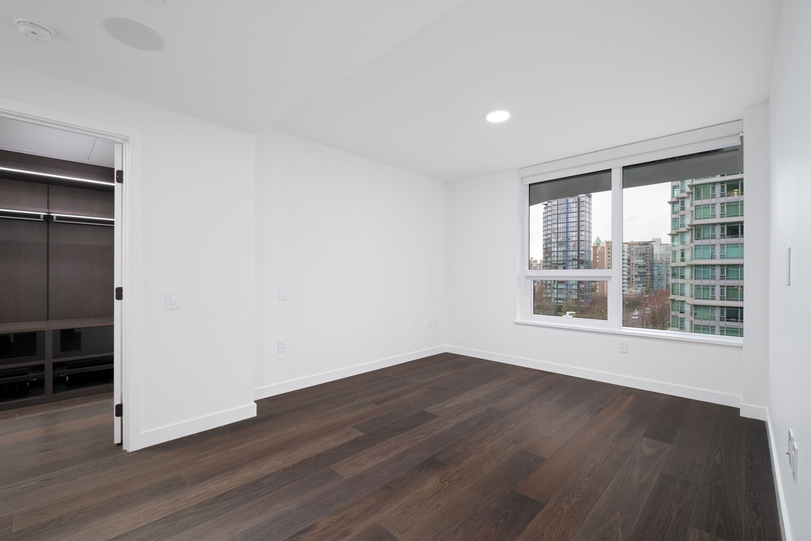 bedroom with white walls and dark hardwood flooring in rental condo at cardero