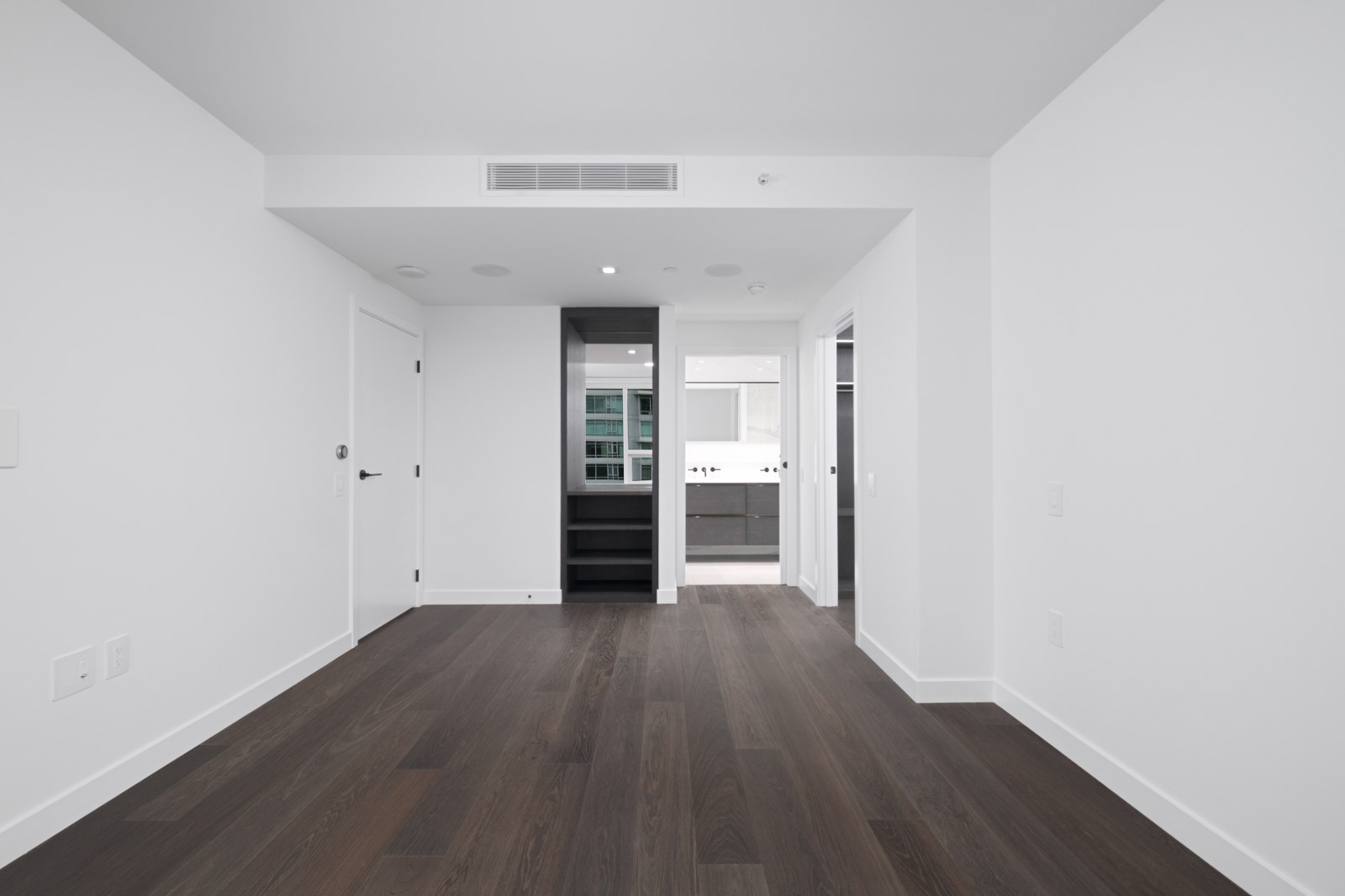 bedroom with dark hardwood flooring and white walls and open closet door in rental condo at cardero building in downtown vancouver bc