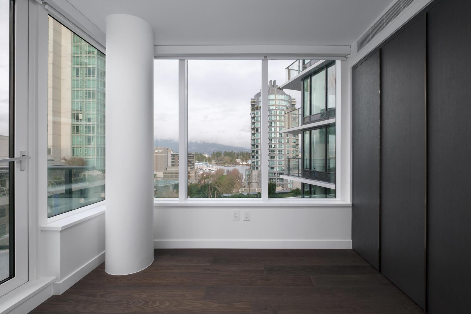 room with bright windows and white round pillar on left in rental condo at cardero in downtown vancouver