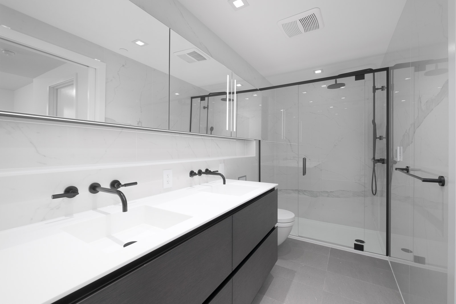 bathroom with white countertops and tiling and clear shower door in rental condo at cardero in downtown vancouver bc