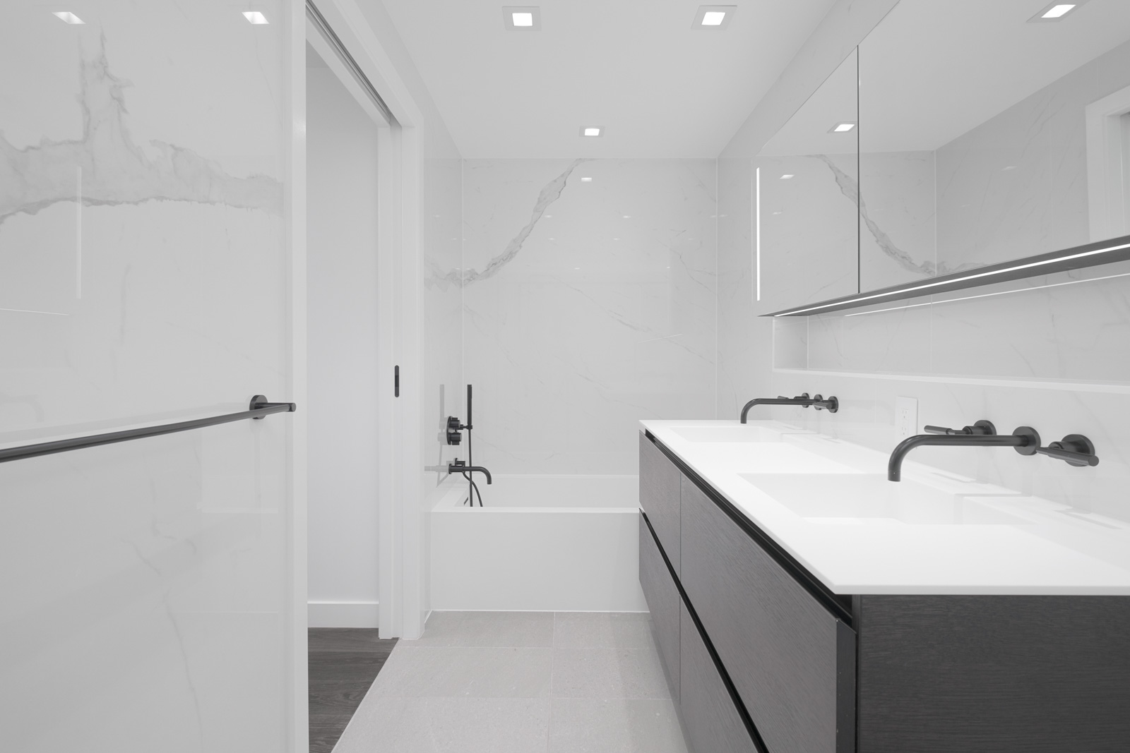 bathroom with mirror and vanity on right and bathtub in background in rental condo at cardero in downtown vancouver