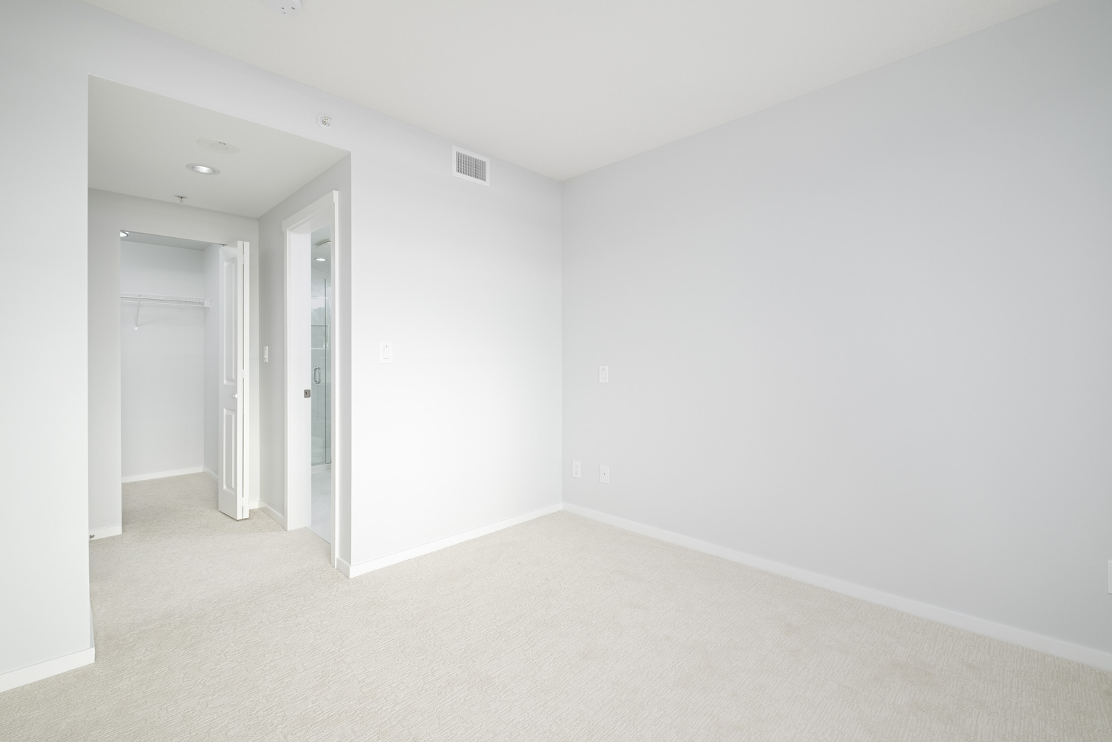 bedroom with white walls and hardwood floors in rental condo in the Metrotown neighbourhood of Burnaby