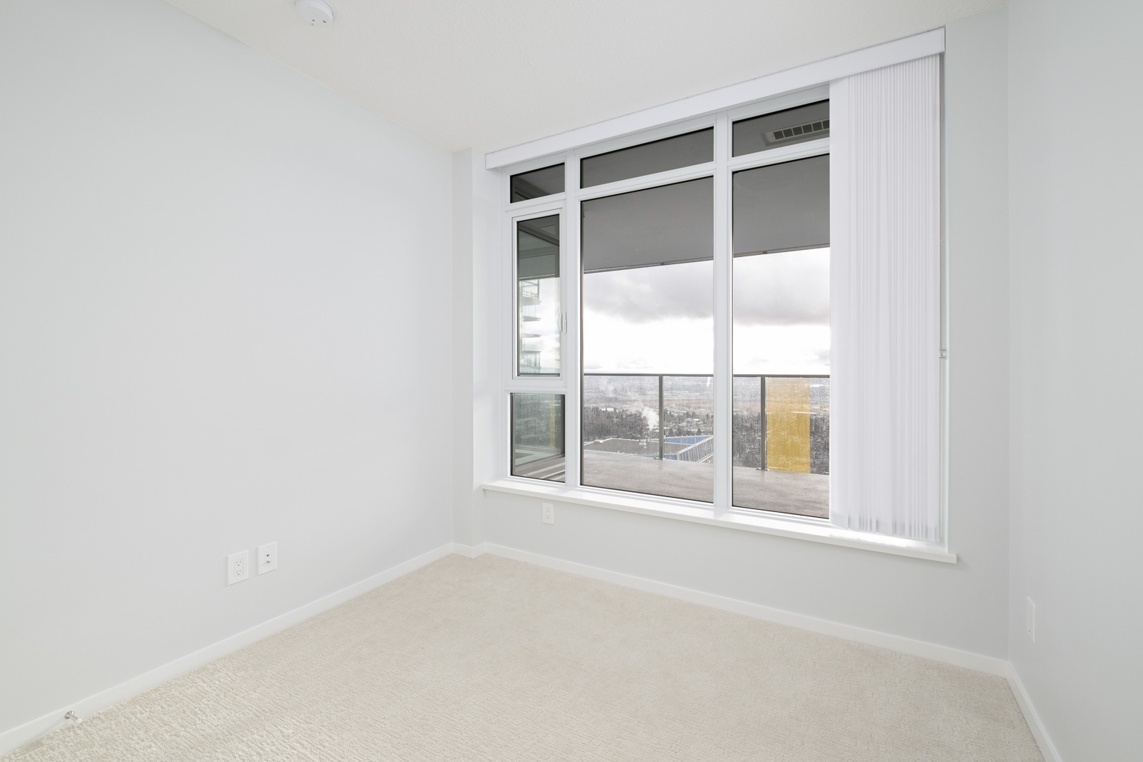 bedroom with white walls and window in rental condo in the Metrotown neighbourhood of Burnaby