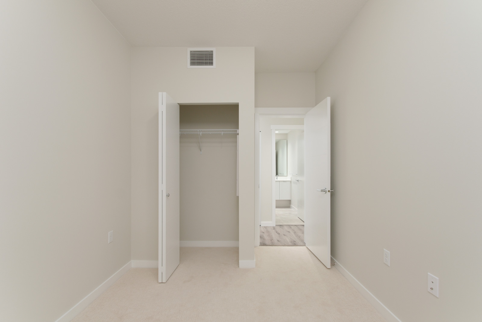 bedroom with walk in closet on left and entry door on right in rental condo in richmond bc managed by birds nest properties
