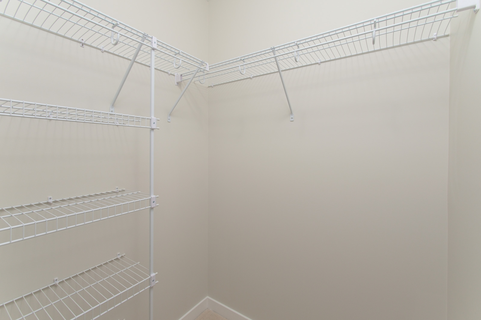 walk in closet with white wire rack shelving in rental condo apartment near garden city in richmond bc