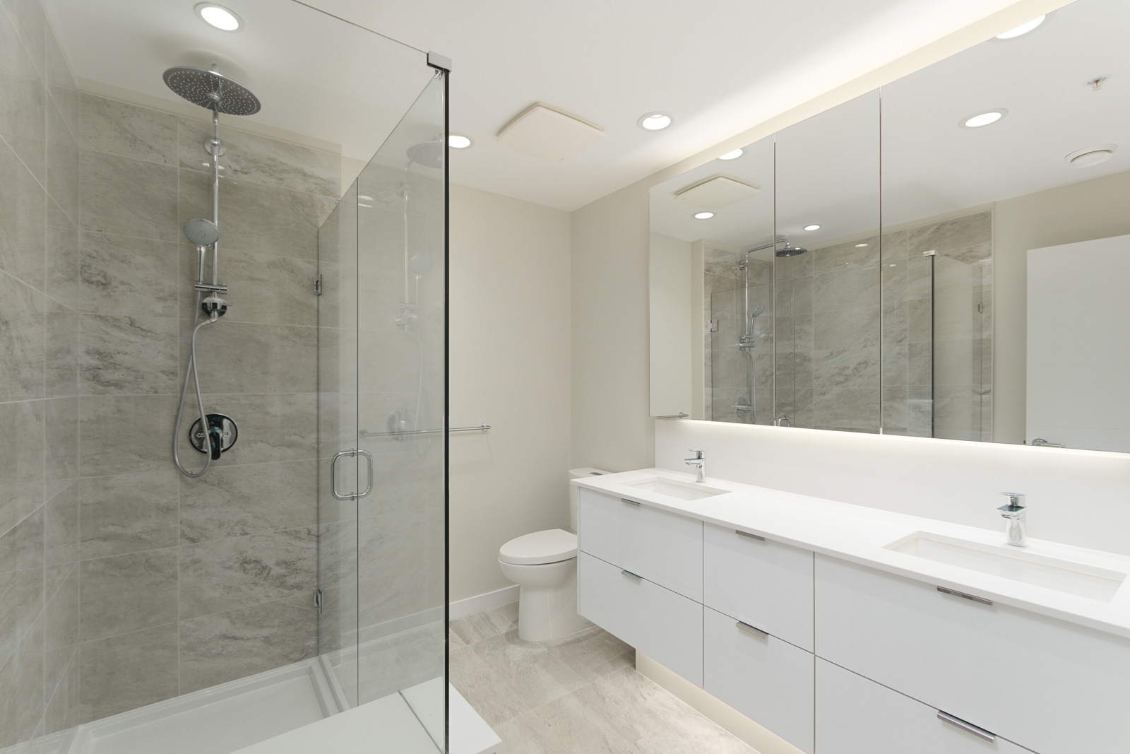 bathroom with glass shower walls on left and white vanity and mirror on right in rental condo in richmond bc