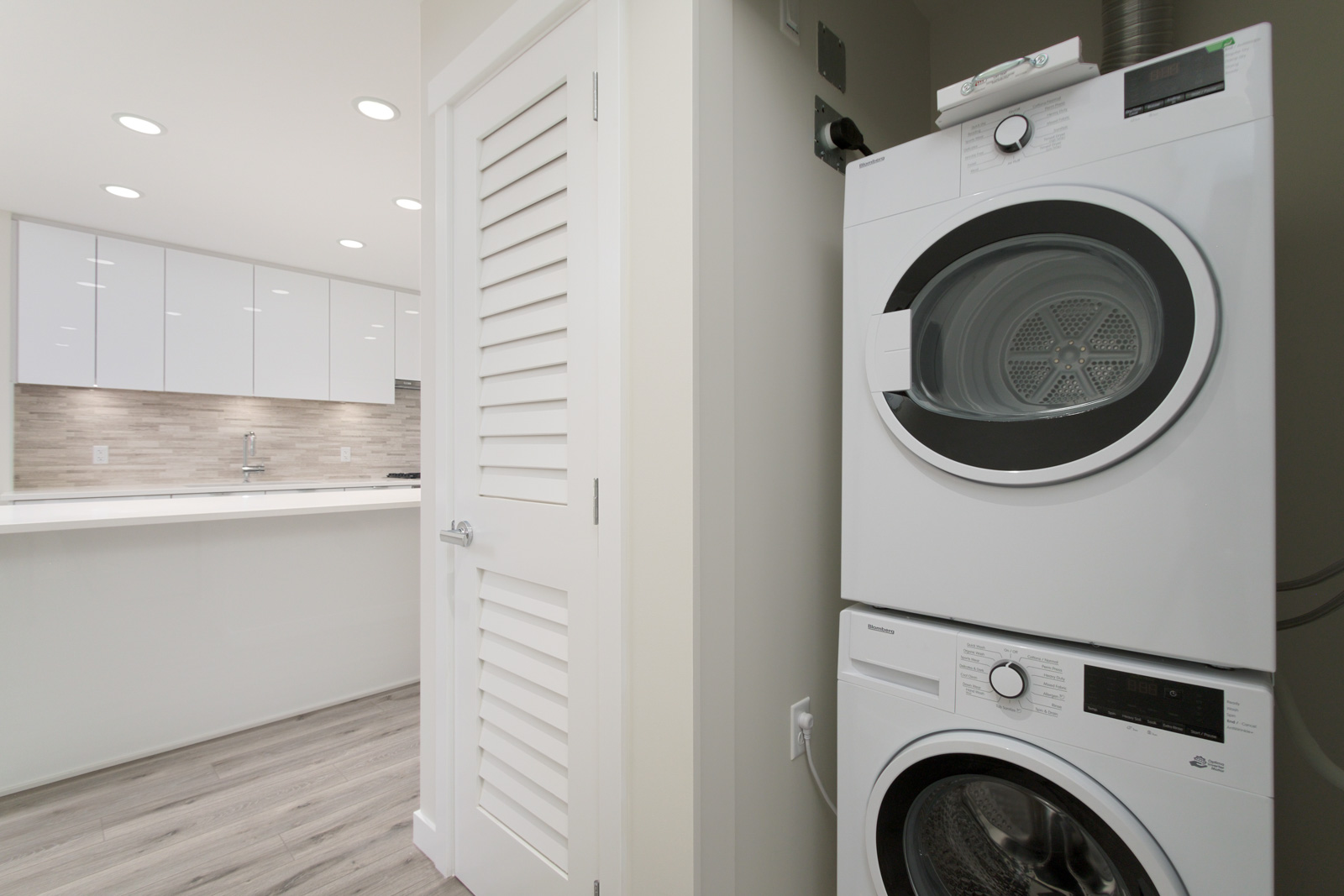 stacked white washer and dryer on right in laundry closet with view of ktichen on left in rental condo near garden city in richmond bc