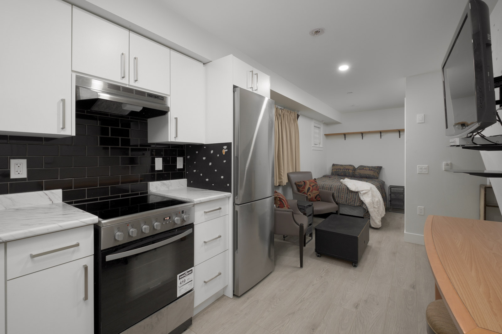 kitchen with laminate flooring with steel fridge in norquay east vancouver