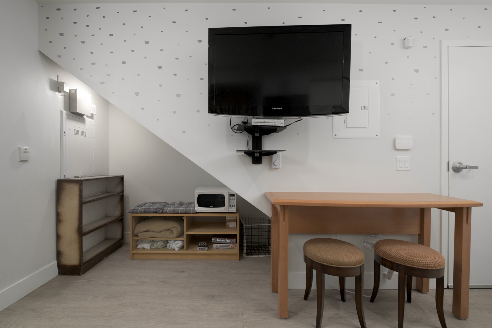 living room with tv embedded on the wall with brown table and stool with white walls at east vancouver
