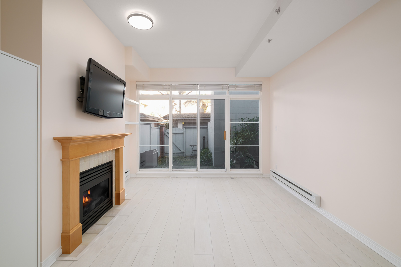 fireplace on right and windows to back patio in kitsilano rental townhome managed by birds nest properties