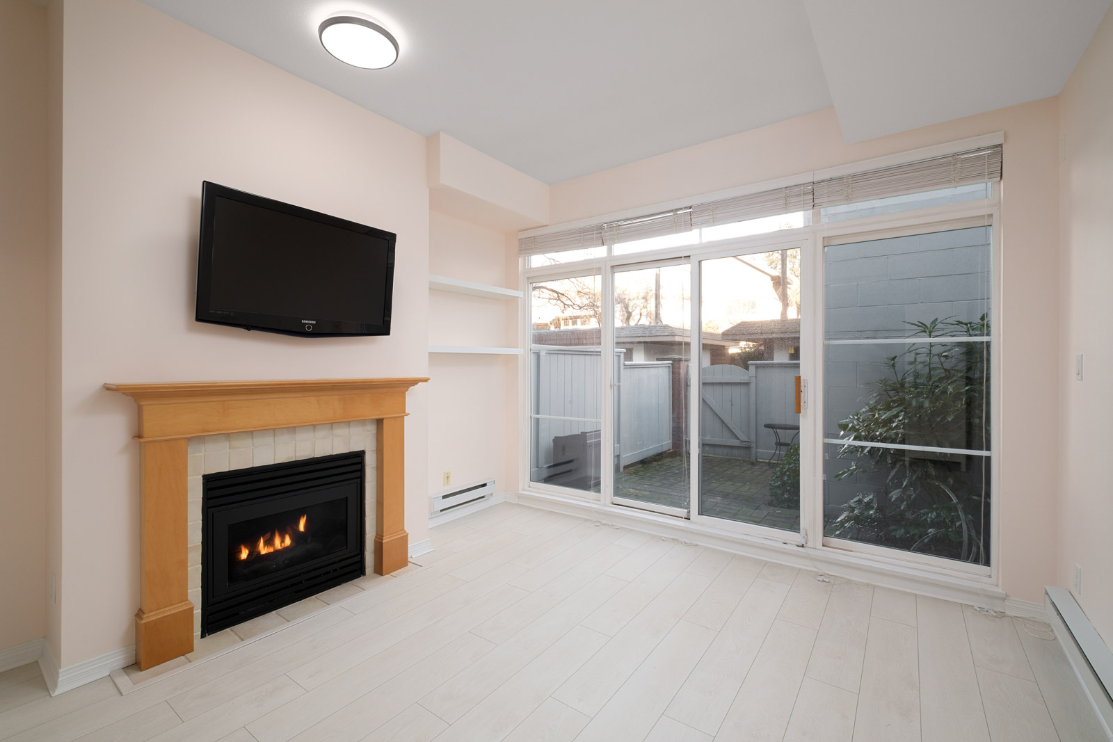 fireplace on right in living room and view to back patio in kitsilano rental townhome managed by birds nest properties