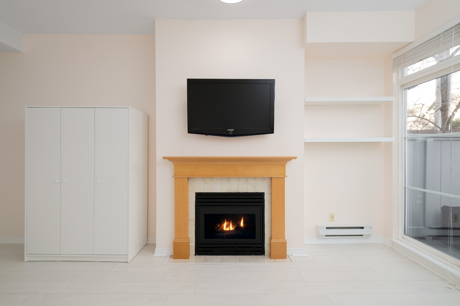 fireplace with tv on top in living room in kitsilano rental townhome managed by birds nest properties