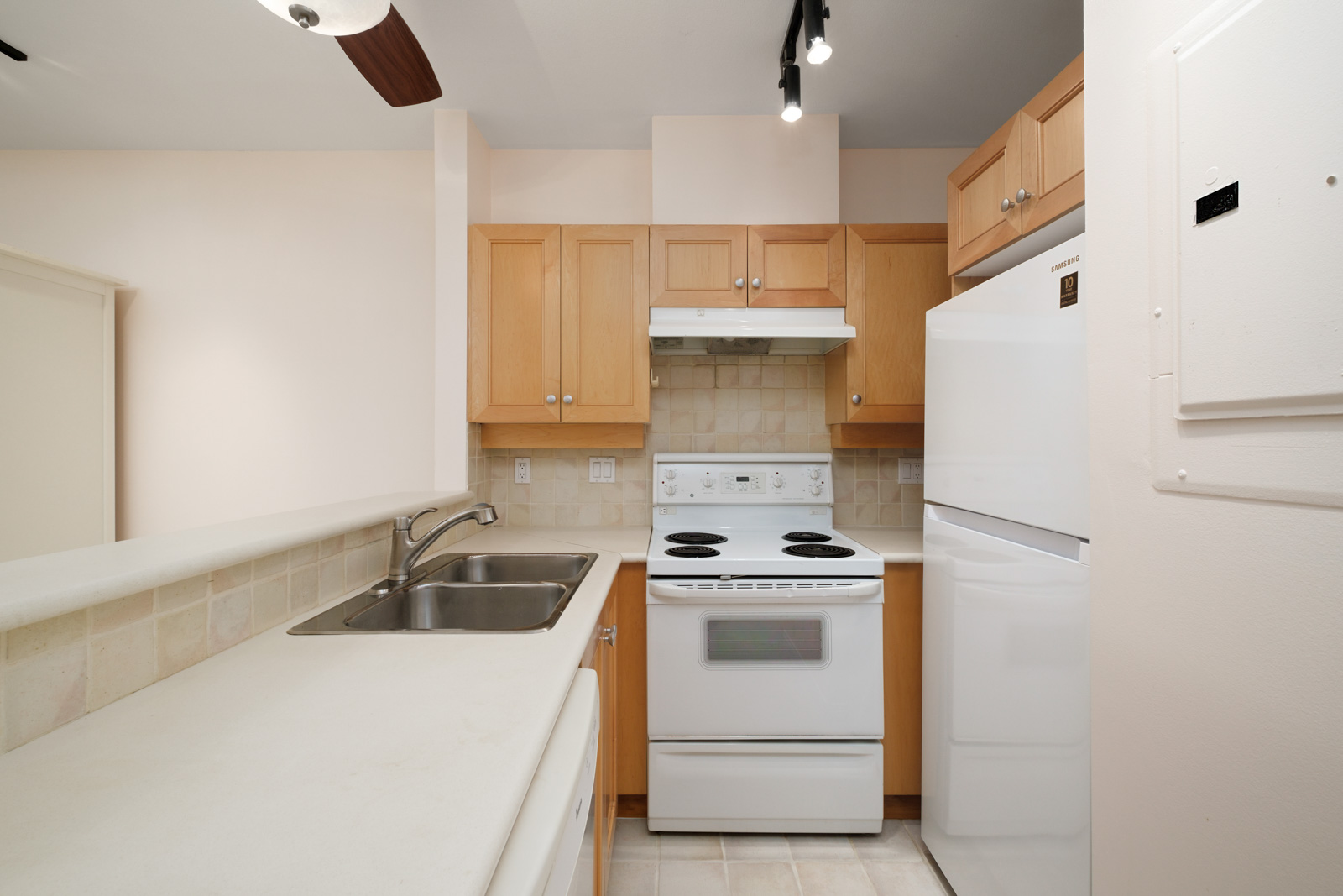 kitchen with white stove and wood cabinets in kitsilano rental studio apartment in vancouver westside