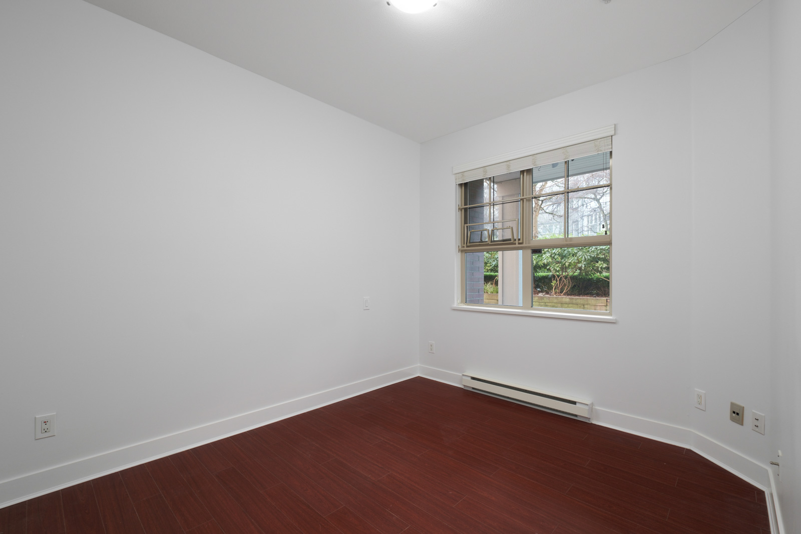 bedroom with hardwood flooring and white walls and window on right in rental apartment in alexandra house in shaughnessy of vancouver westside