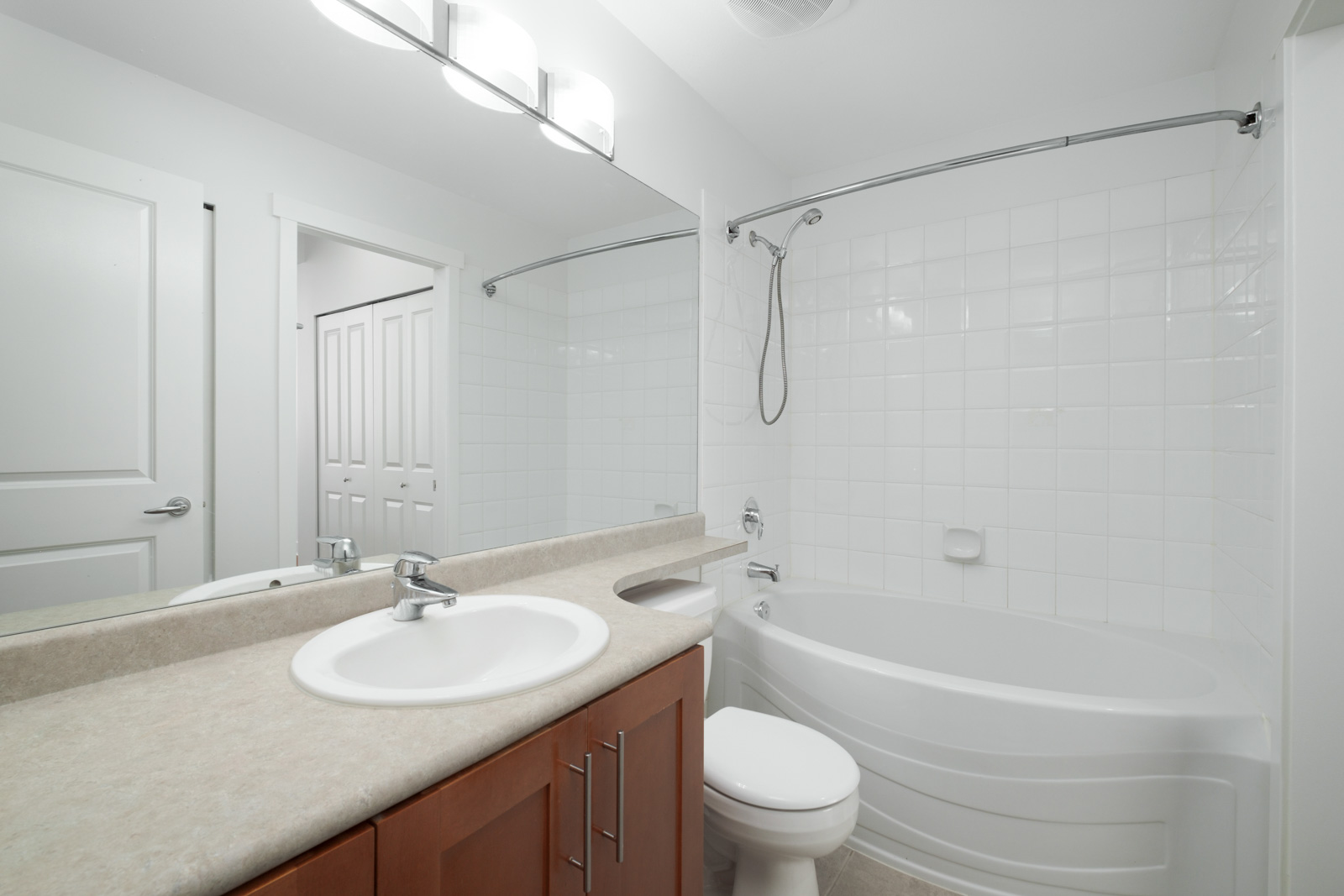 bathroom with vanity and mirror on left and bathtub on right in garden level apartment in alexandra house in shaughnessy of vancouver westside