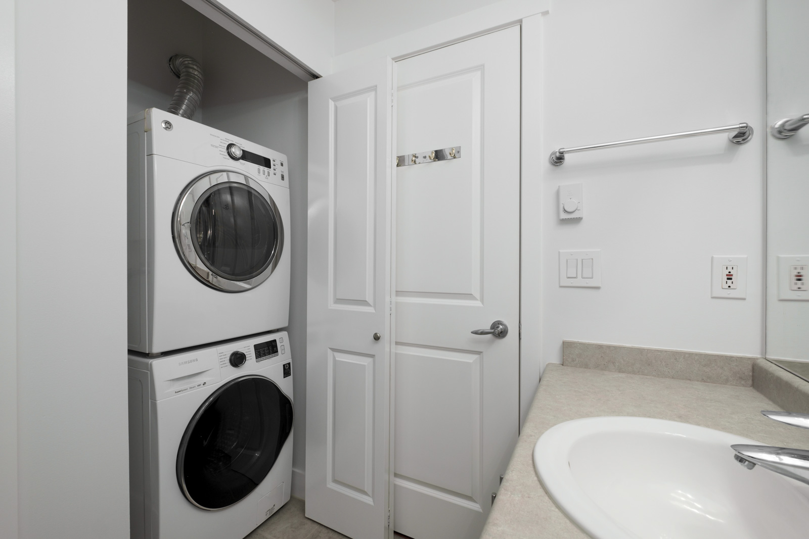 stacked white washer and dryer in closet in rental apartment at alexandra house in shaughnessy of vancouver westside