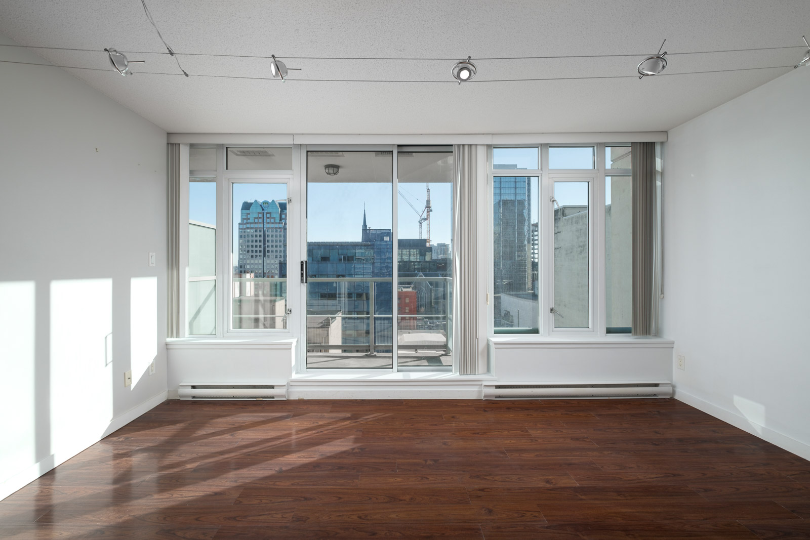 view of city life looking through floor to ceiling in downtown vancouver neighbourhood
