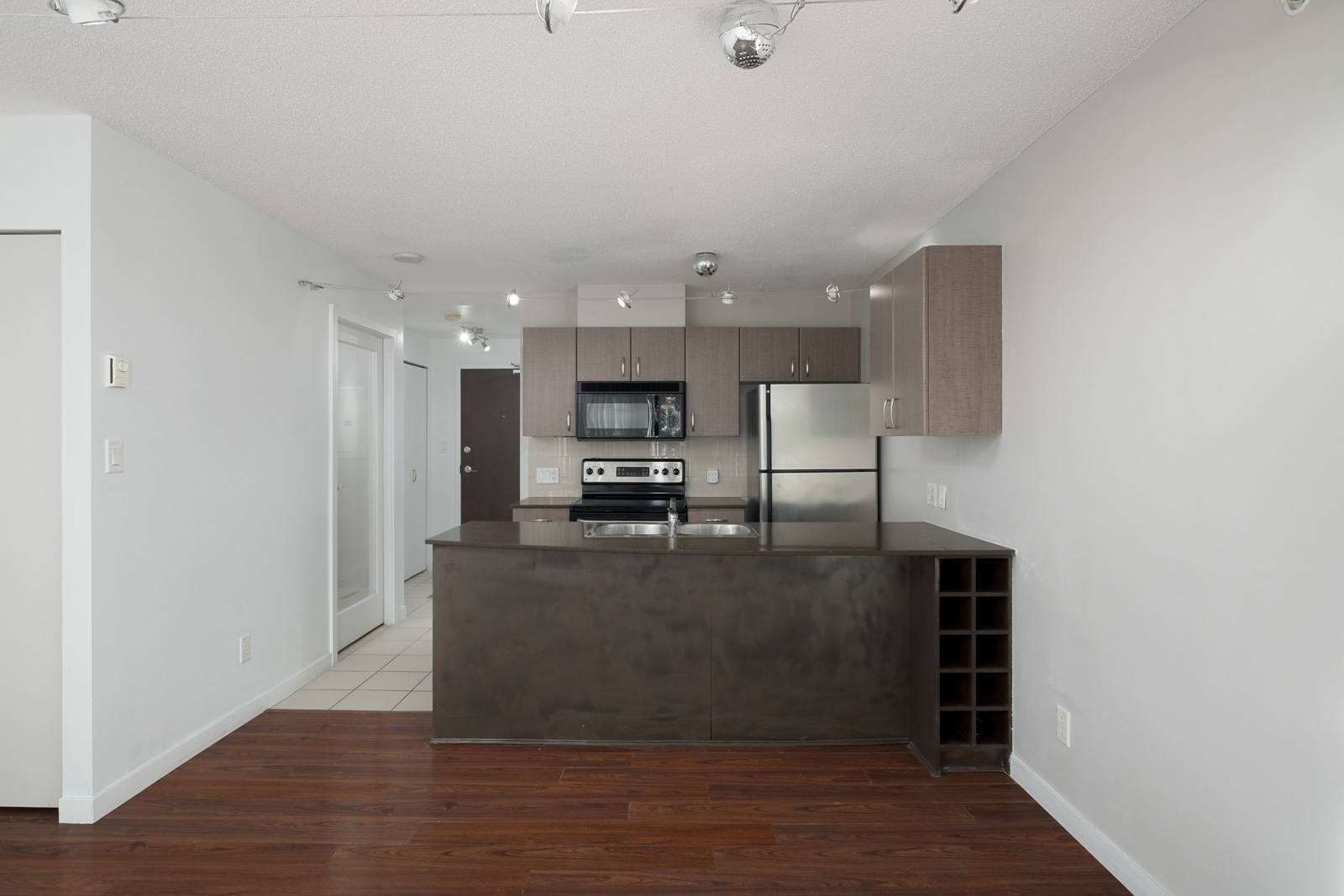kitchen and living room view with hardwood flooring in rental condo in the downtown vancouver neighbourhood