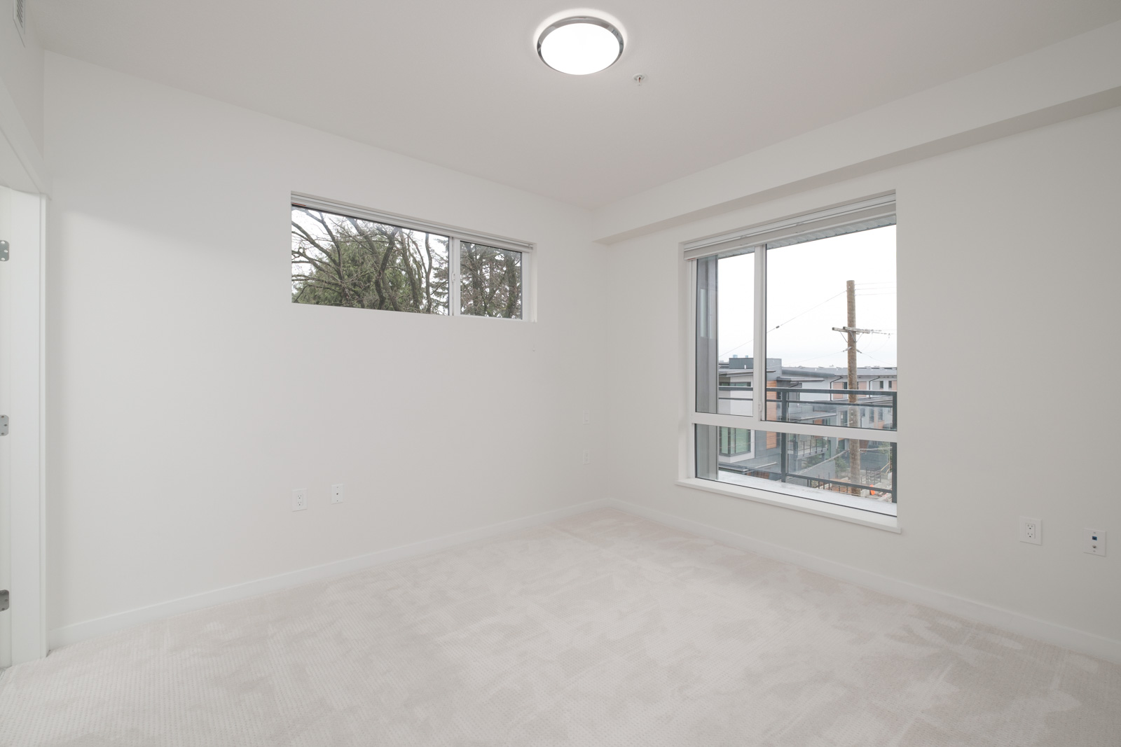 bedroom with white walls and window in rental condo in the Lonsdale neighbourhood of North Vancouver