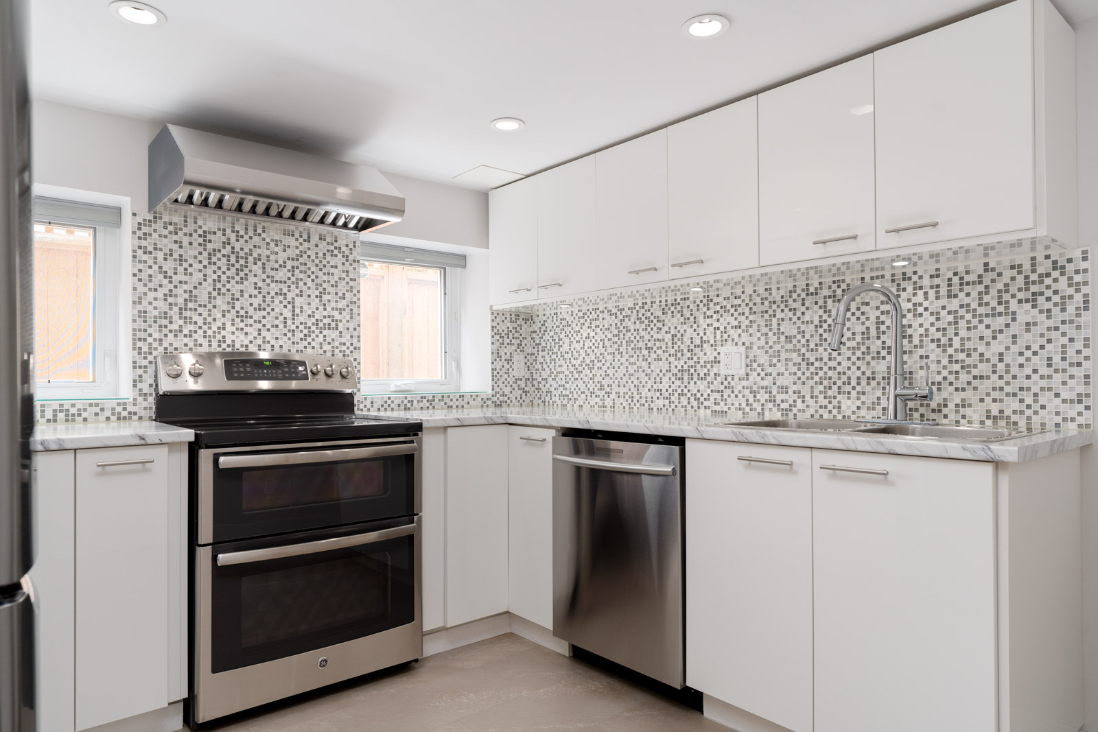 Kitchen equipped with complete stainless steel appliances in home in Vancouver West