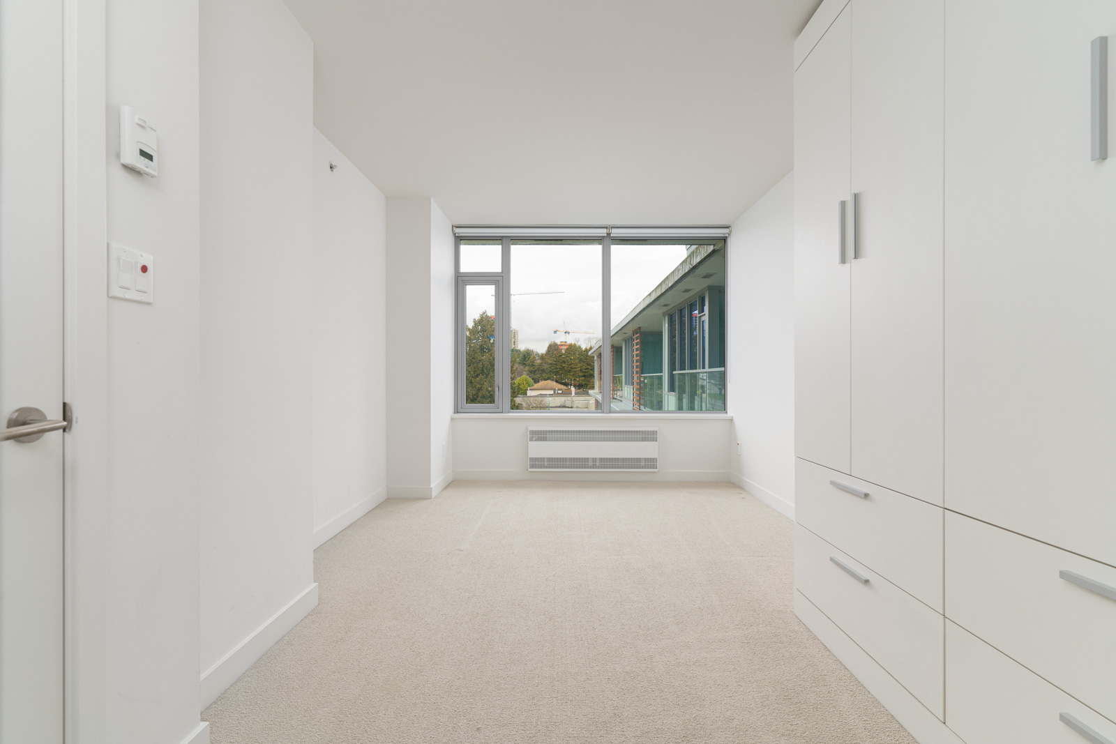 bedroom with white walls in rental house in the Marine Drive neighbourhood of Vancouver